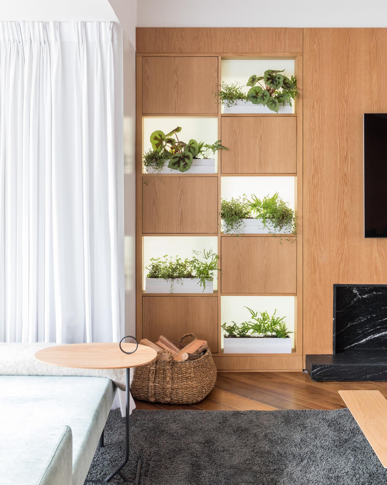 Small planters sit on open shelves within a wood wall.