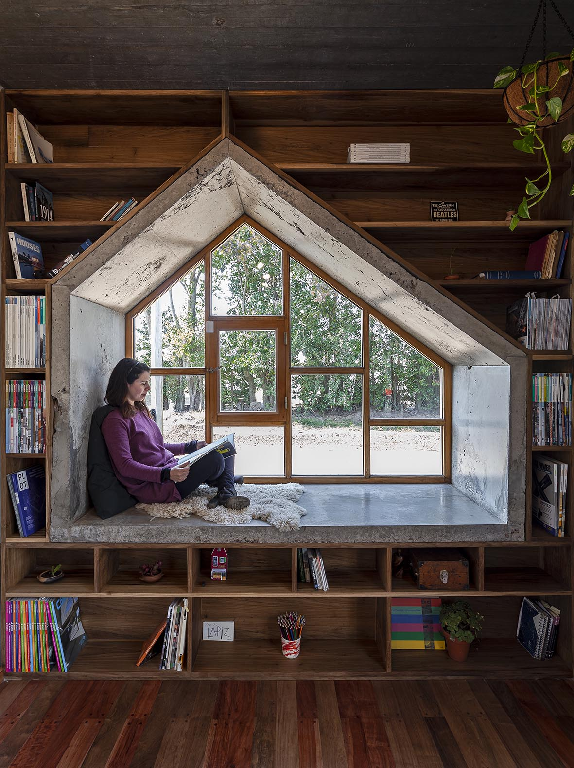 A window seat surrounded by dark wood shelving, has an interior of raw concrete.