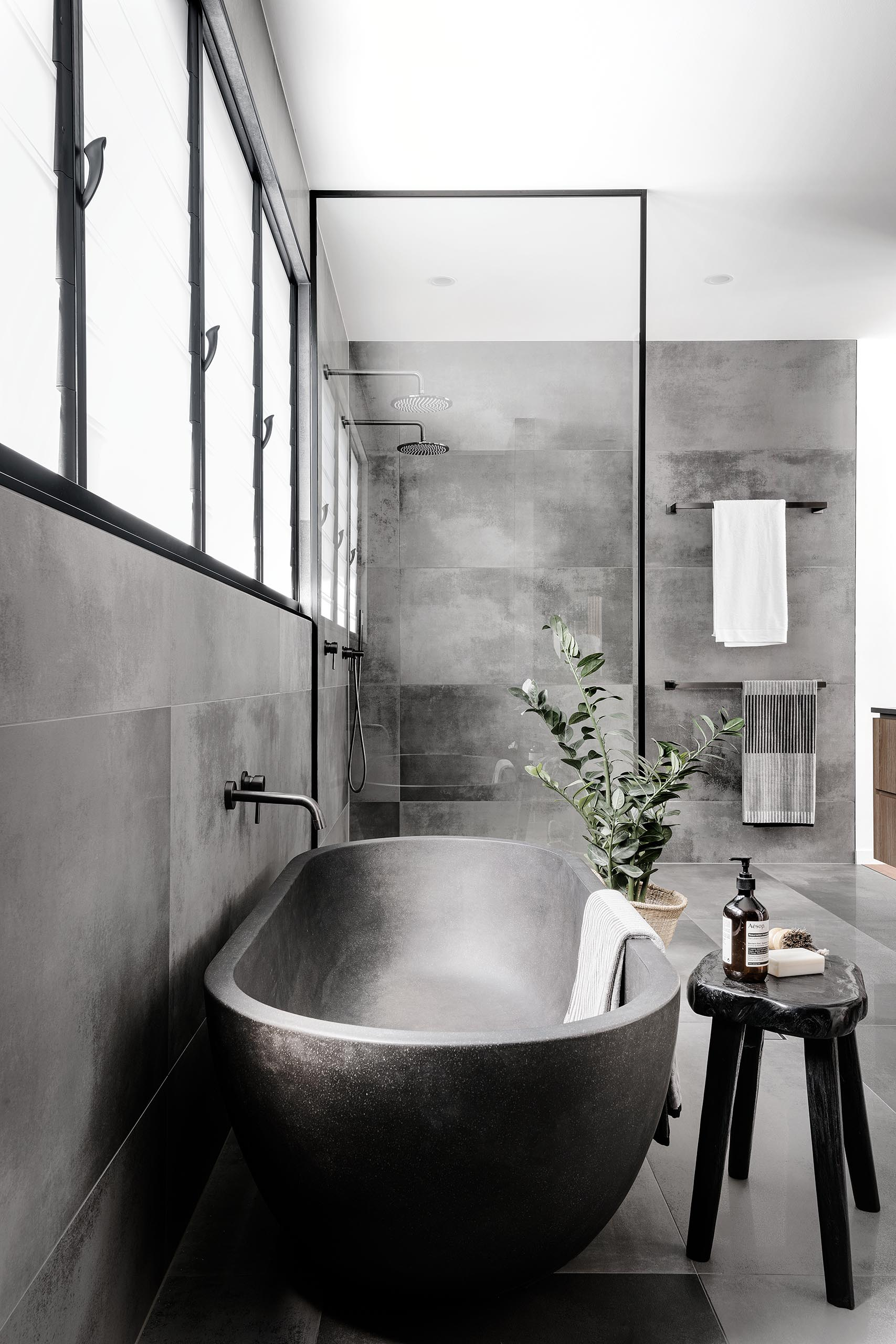 A modern master bathroom with large format grey tiles, a  grey freestanding bathtub, and a black framed glass shower screen.