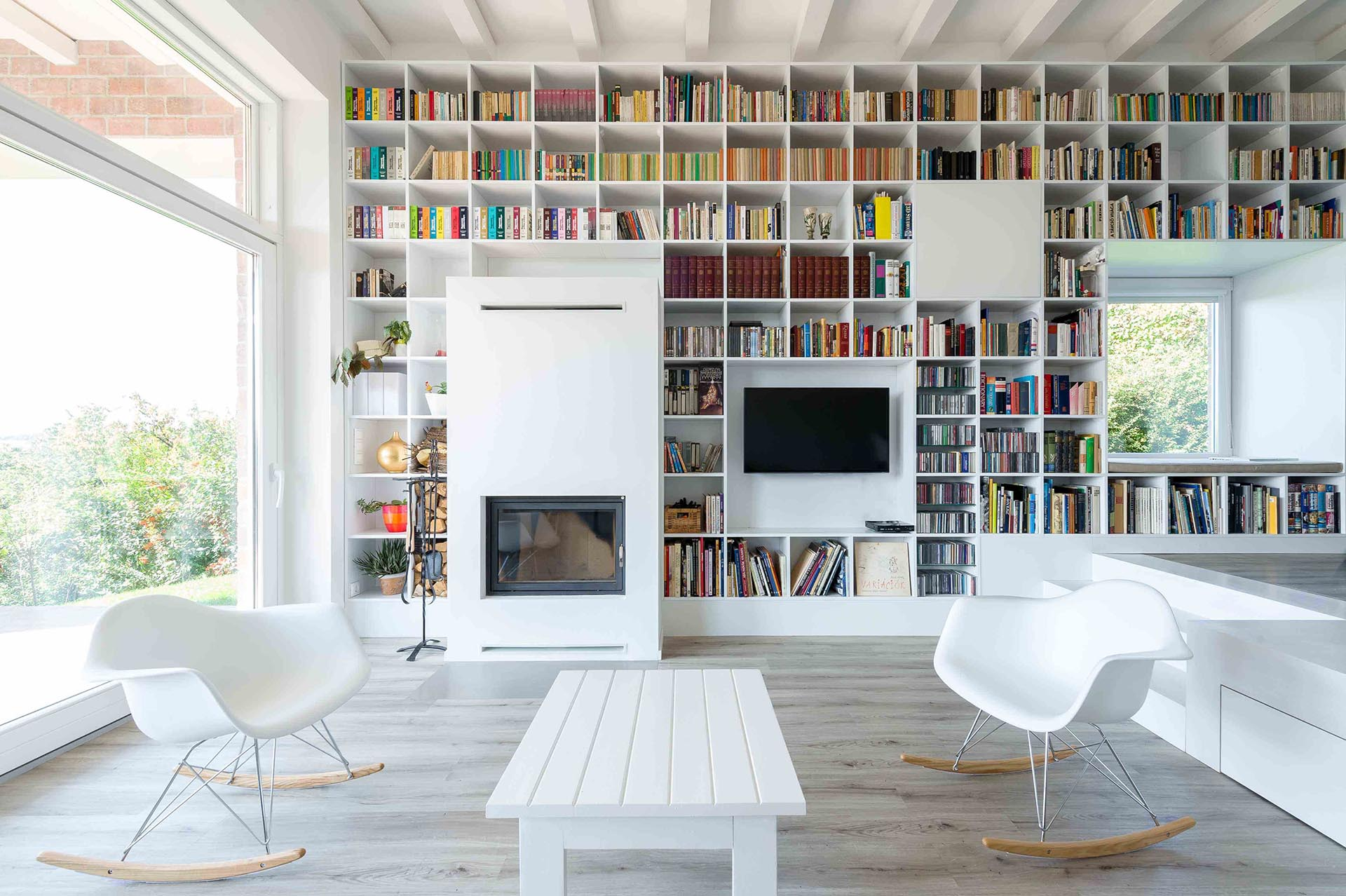 This Long Wall Of Shelving Incorporates Storage, A Fireplace, Windows, And Seating