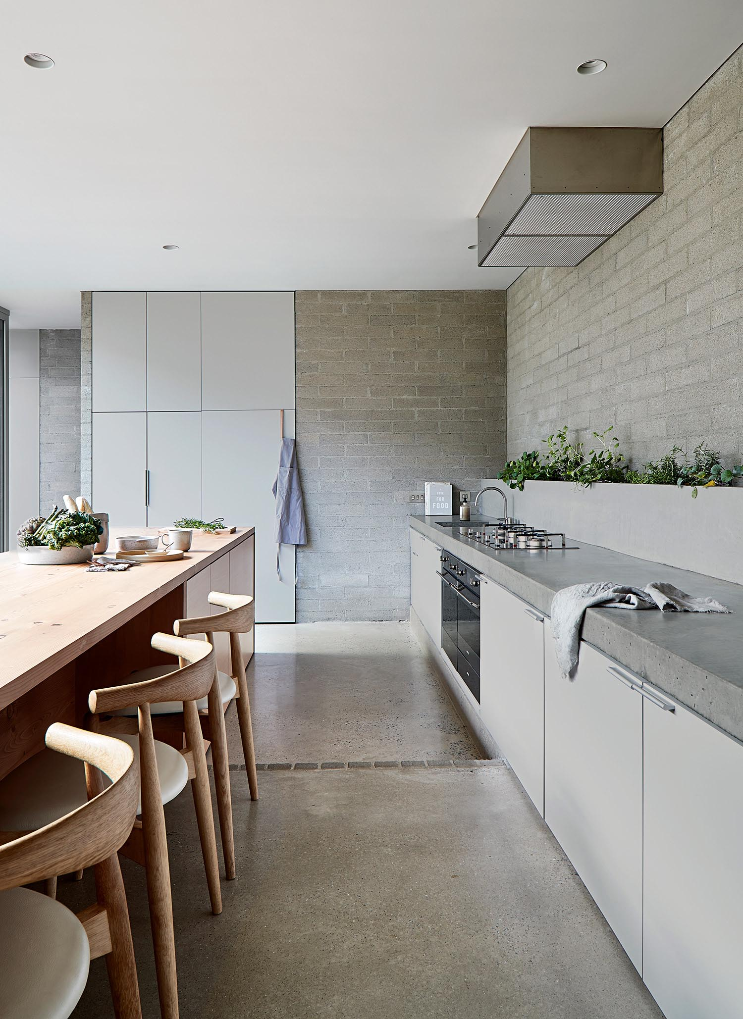 A modern grey kitchen with a wood island and concrete floors.
