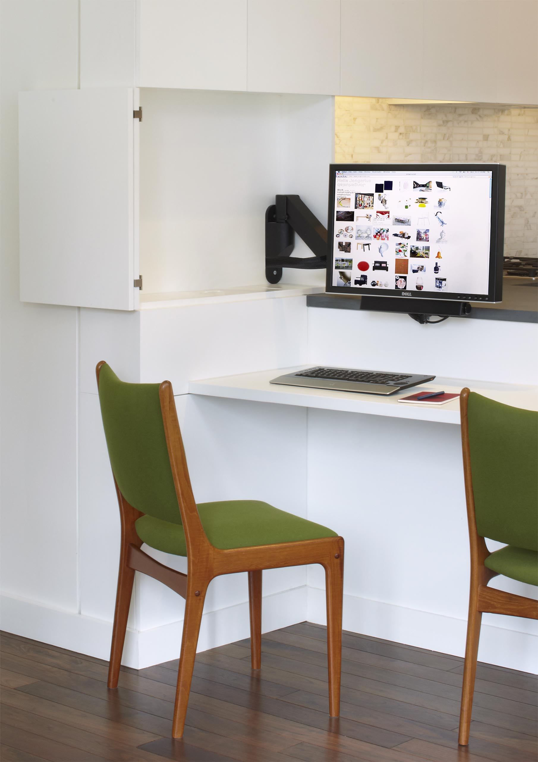 A computer monitor is hidden within the kitchen cabinets, creating a small home office.