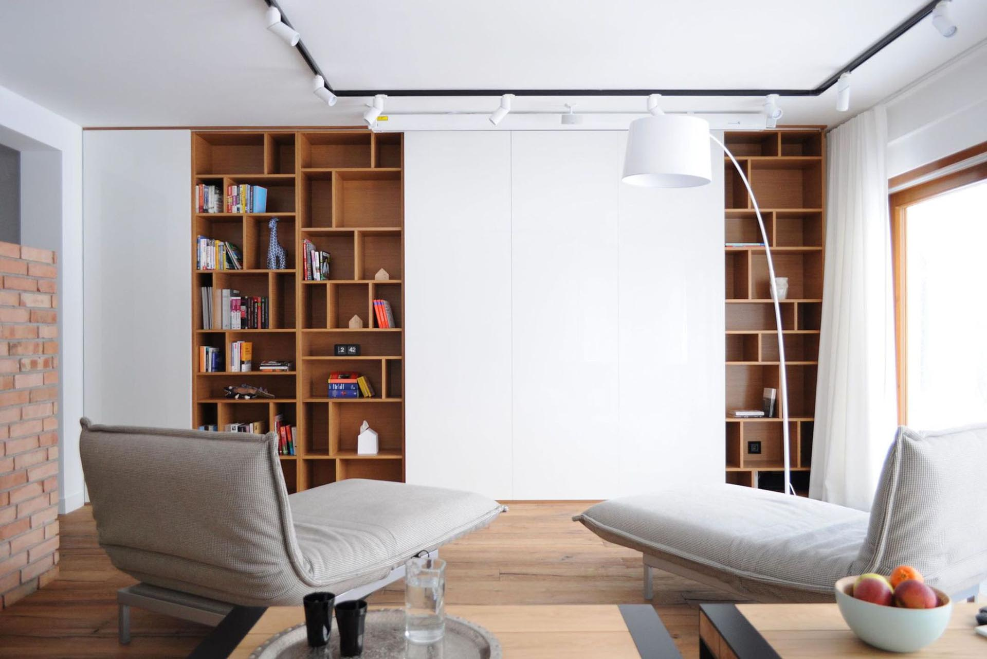 A living room with wood bookshelves has white wall panels that hide a TV.