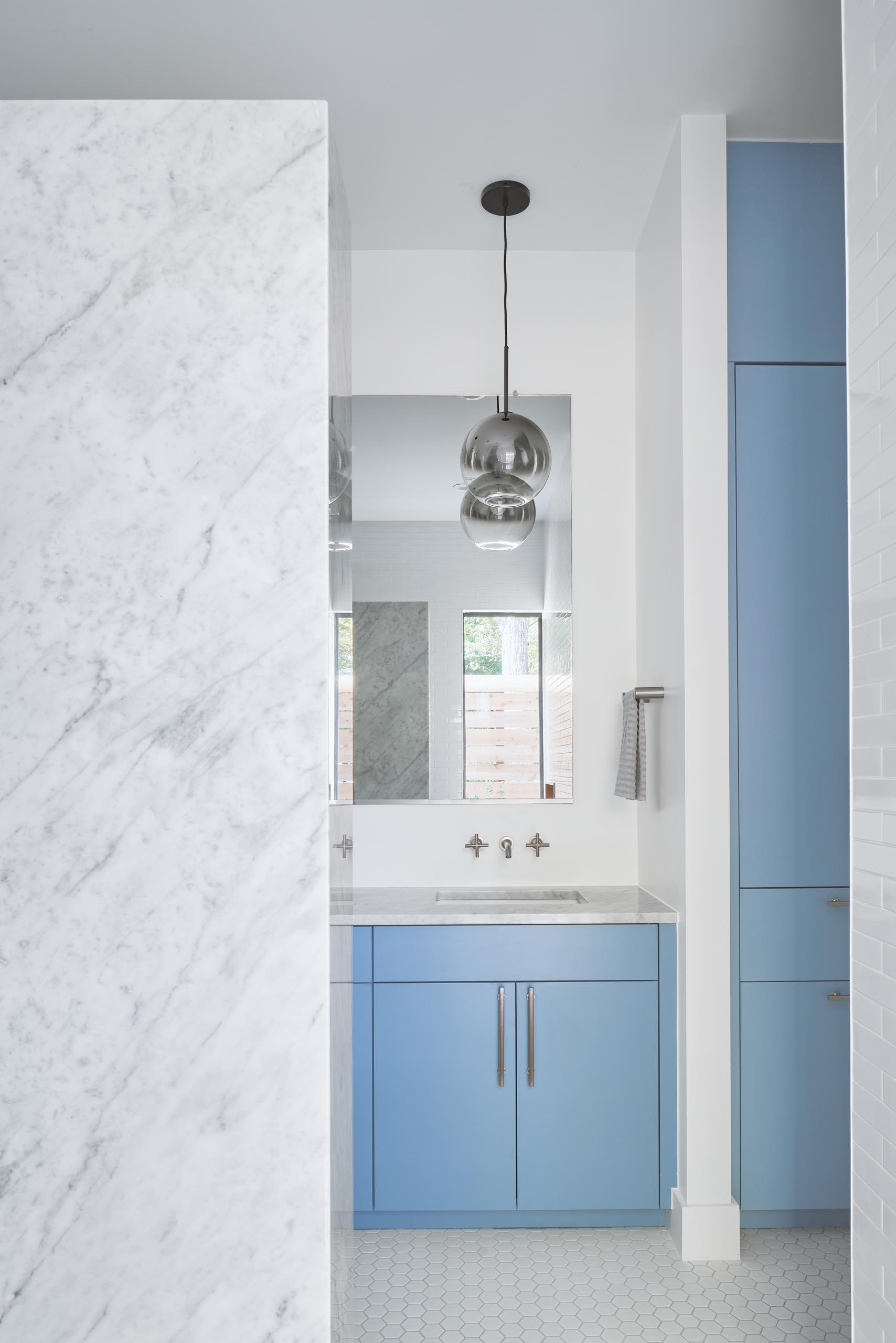 A modern bathroom with a light blue vanity and cabinets, and a marble countertop.