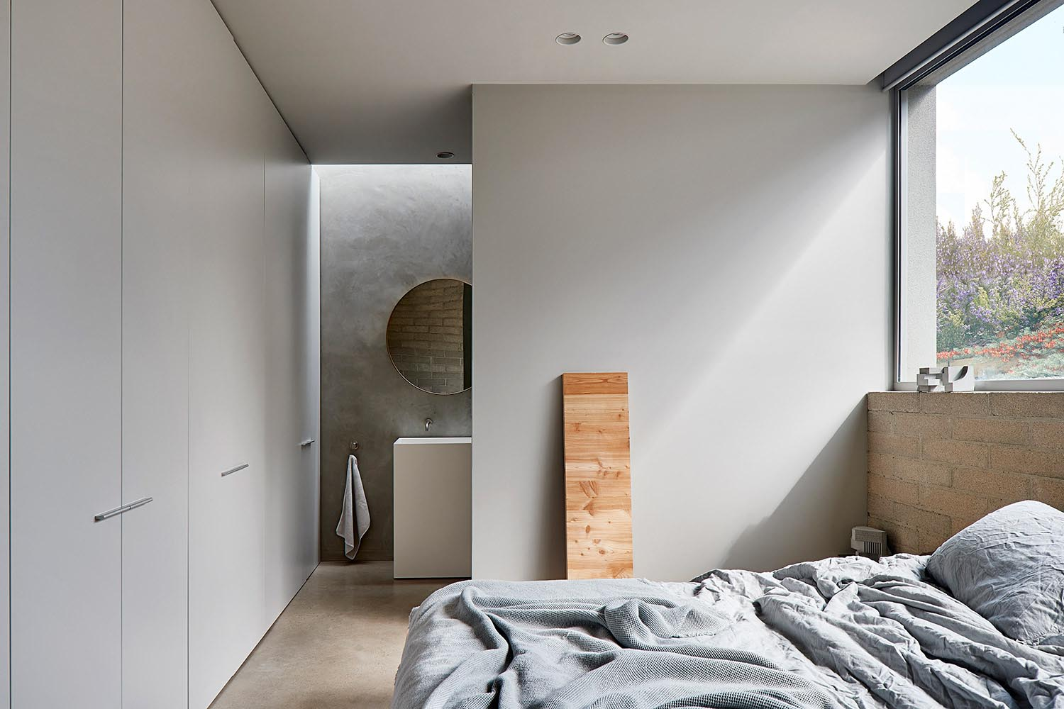 Minimalist bedroom with ensuite bathroom.