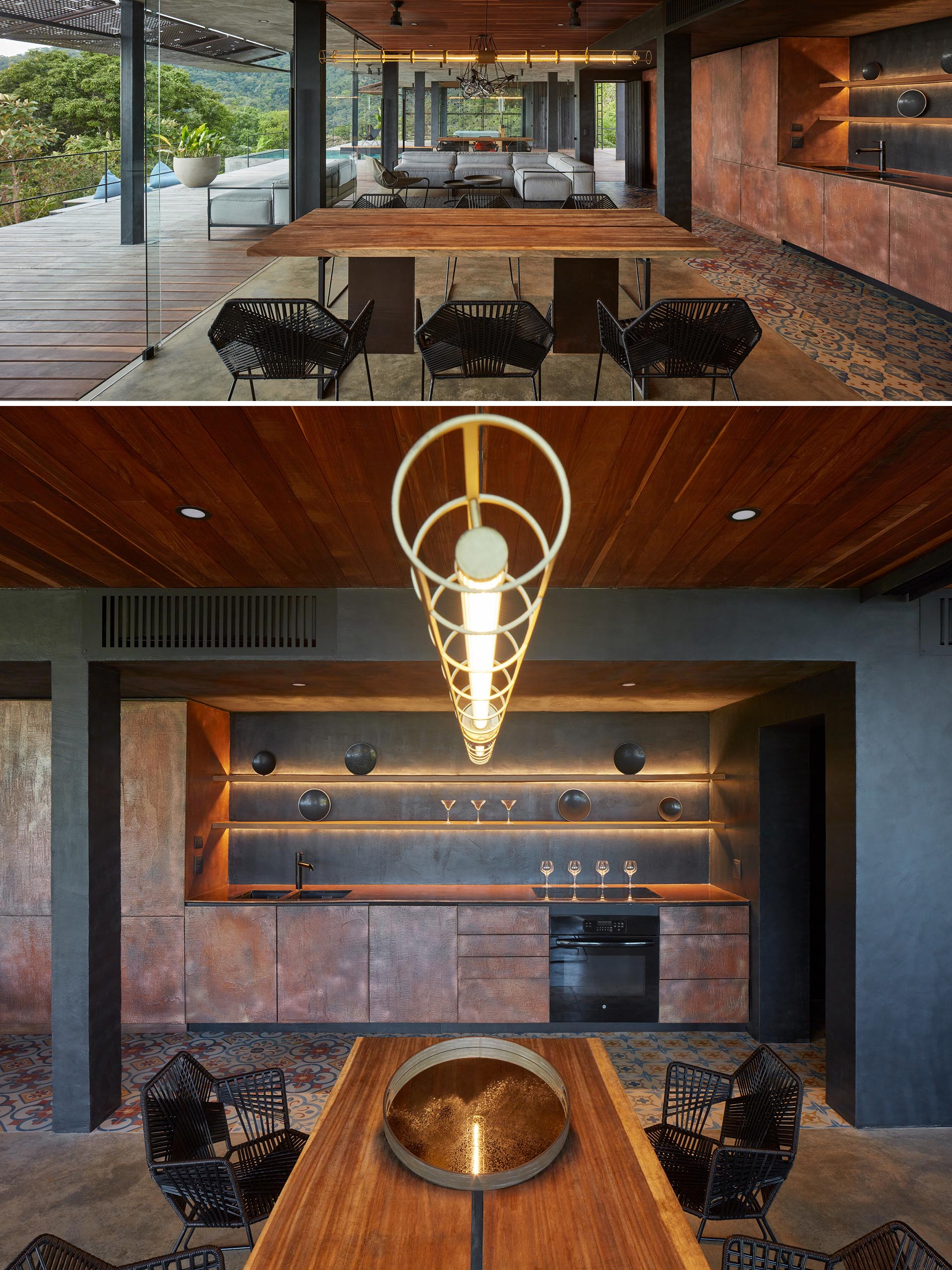 A wood dining table shares an open floor plan with a corten steel kitchen that has backlit shelving.