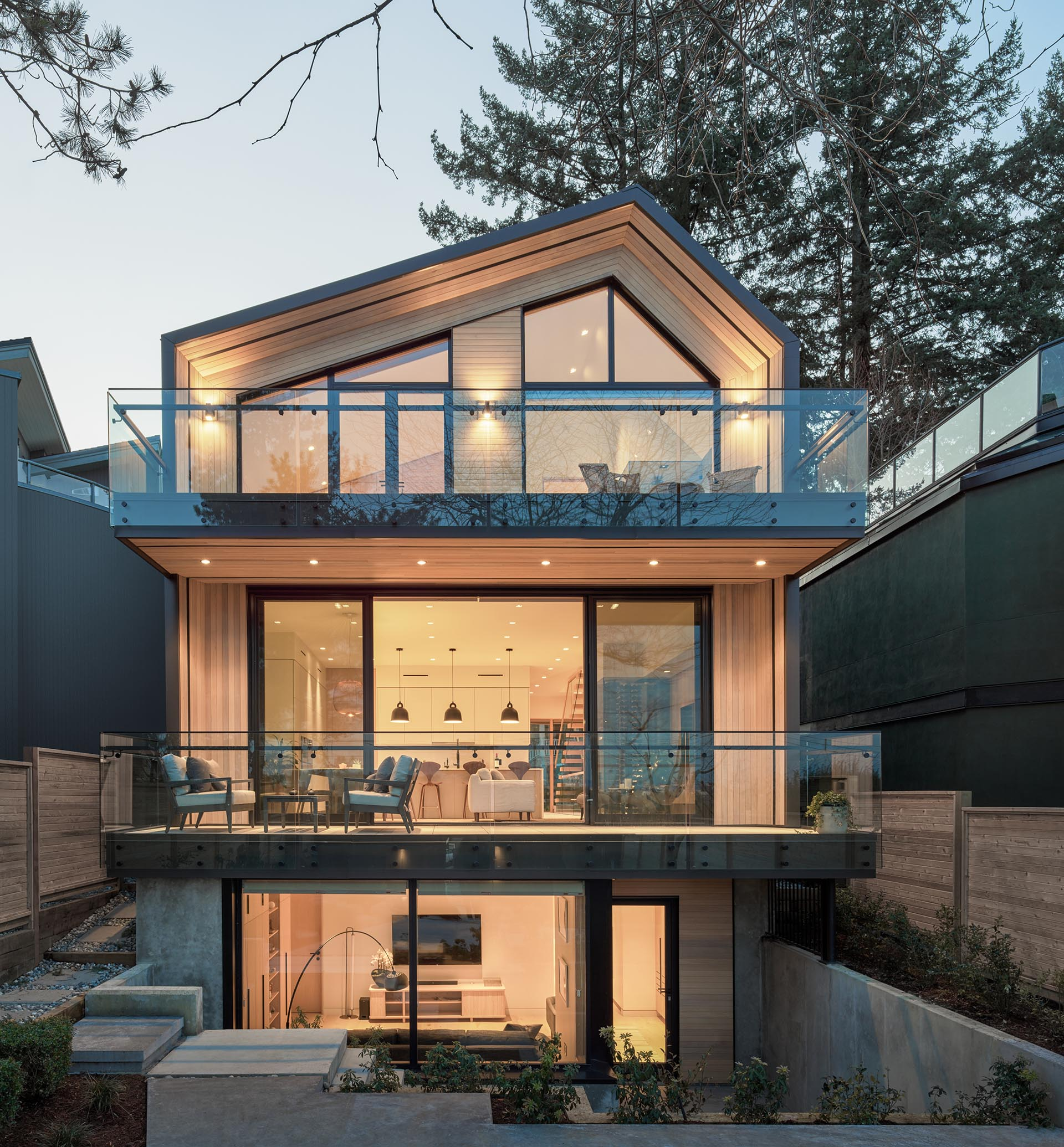 Cedar, black metal, and glass are used to create a contemporary house design.