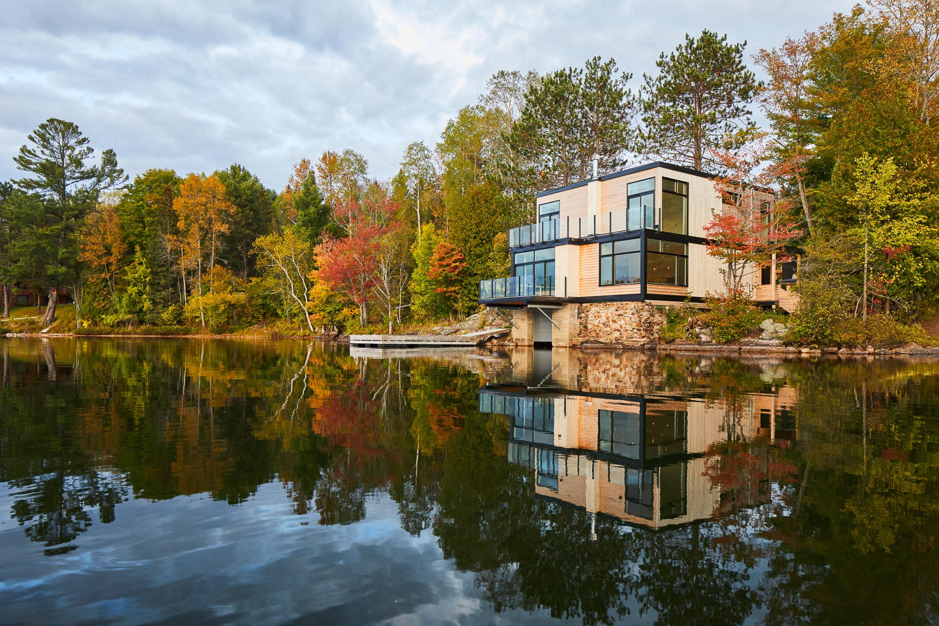 A modern lakefront house with a wood exterior.