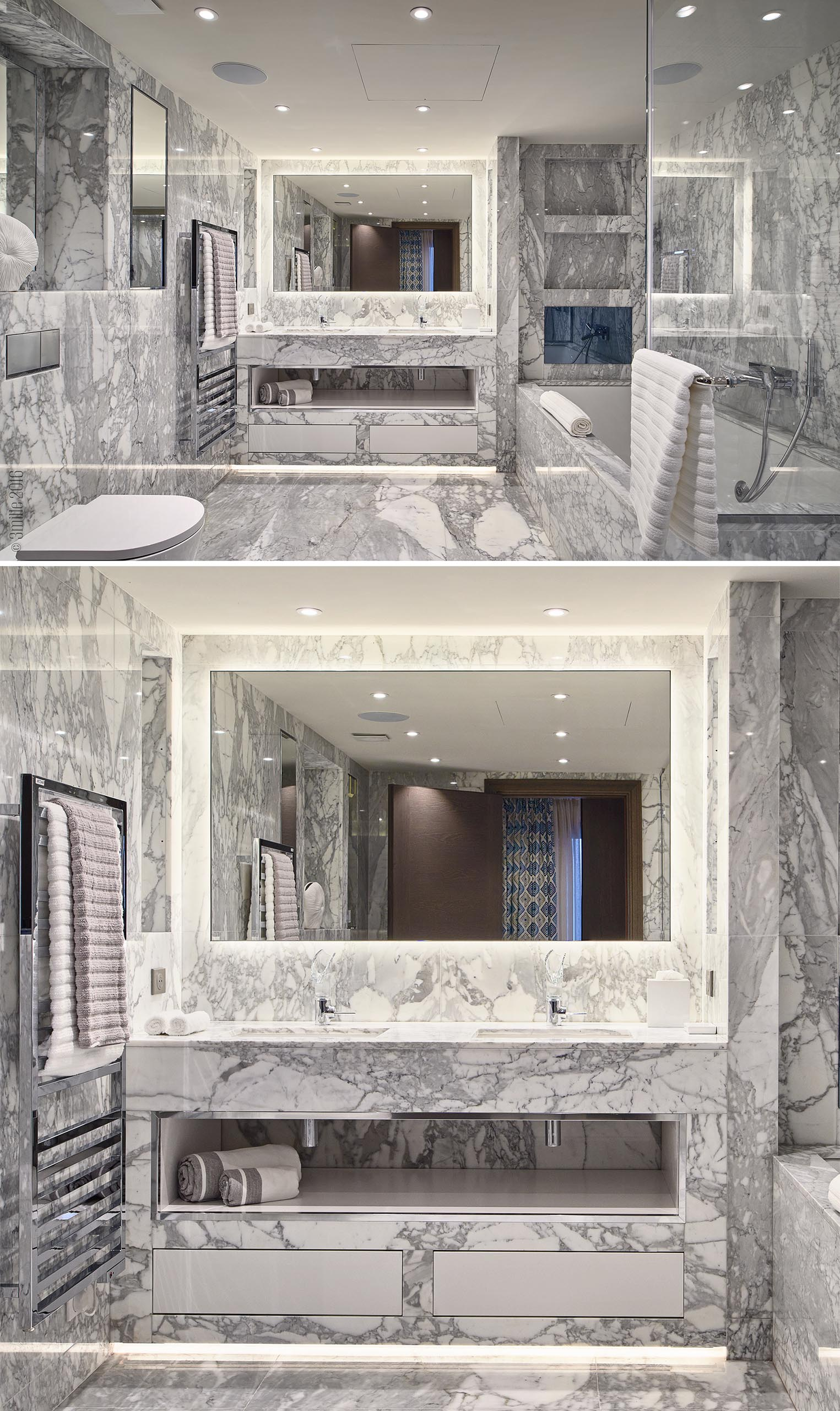 A bathroom with walls and floor covered in grey and white stone.
