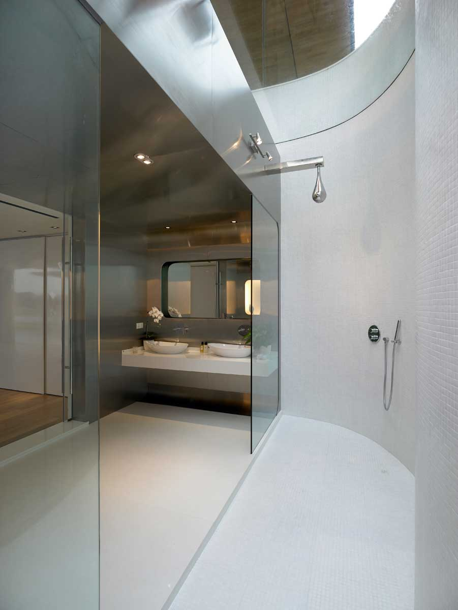 A modern bathroom with stainless steel walls and dual showers with a skylight.