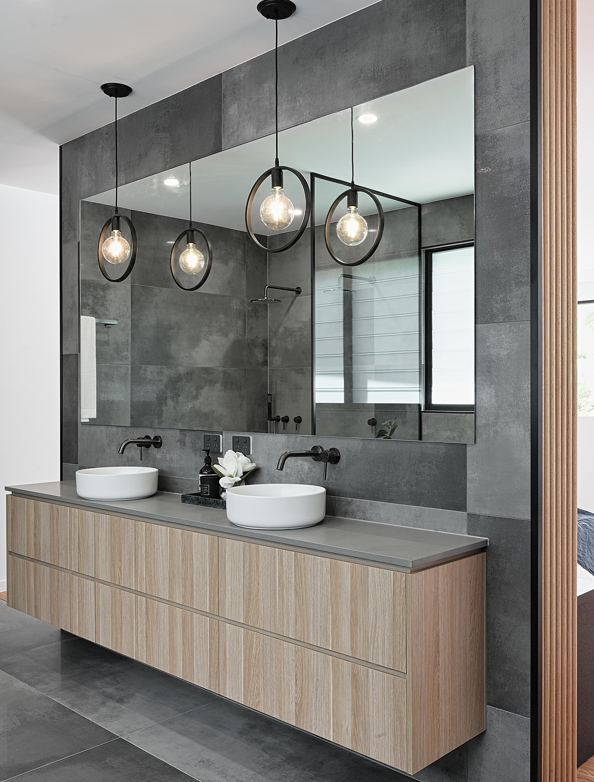 A modern bathroom vanity with wood cabinets, white sinks, a grey countertop, black accents, and two pendant lights.
