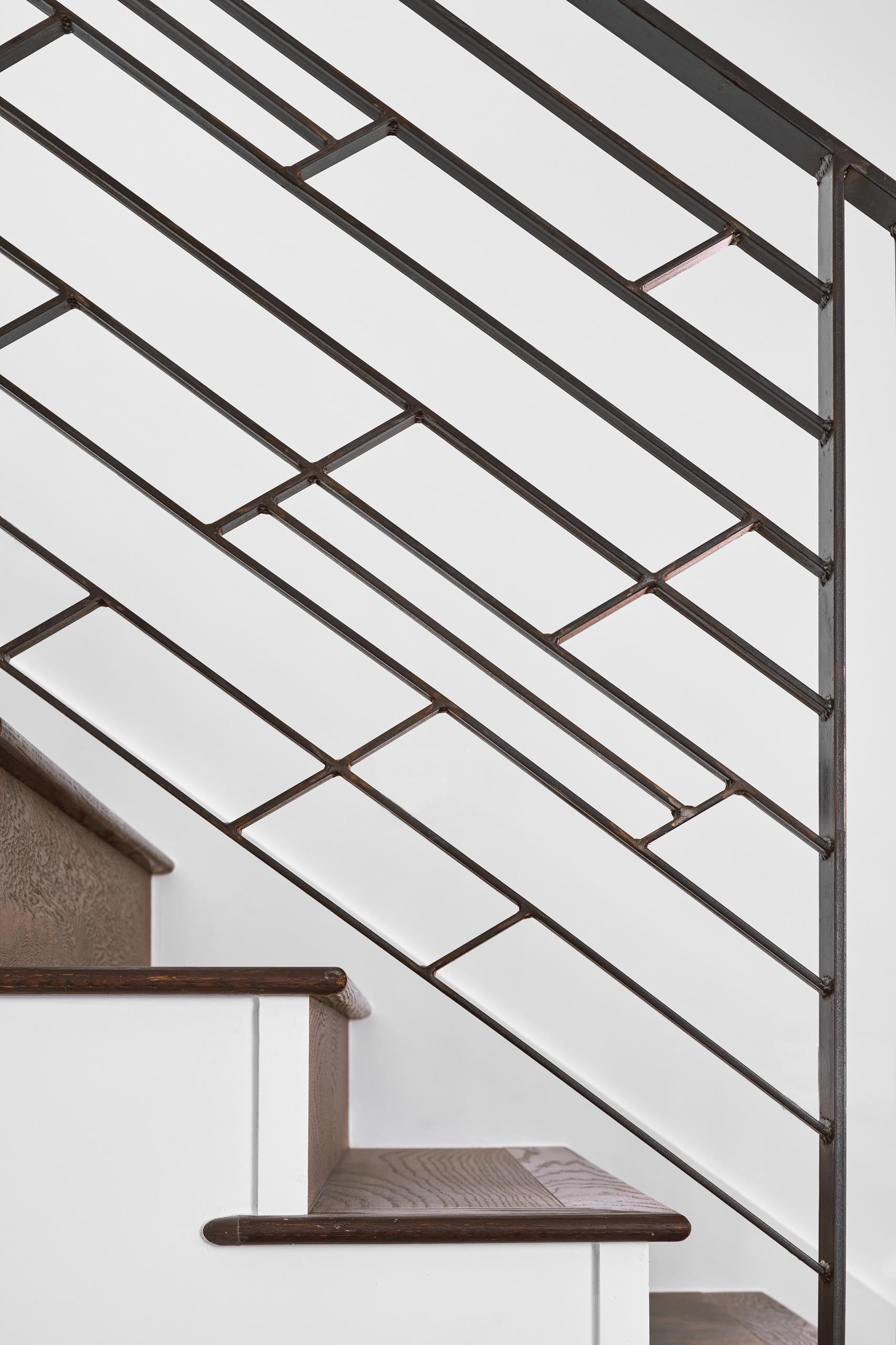 Modern stairs with wood treads and a graphic railing.