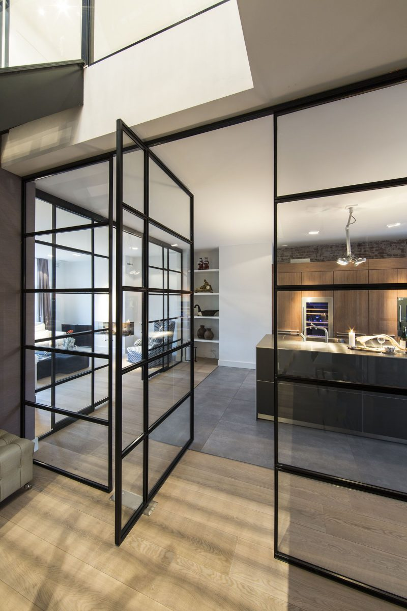 A black framed pivoting glass door and walls.