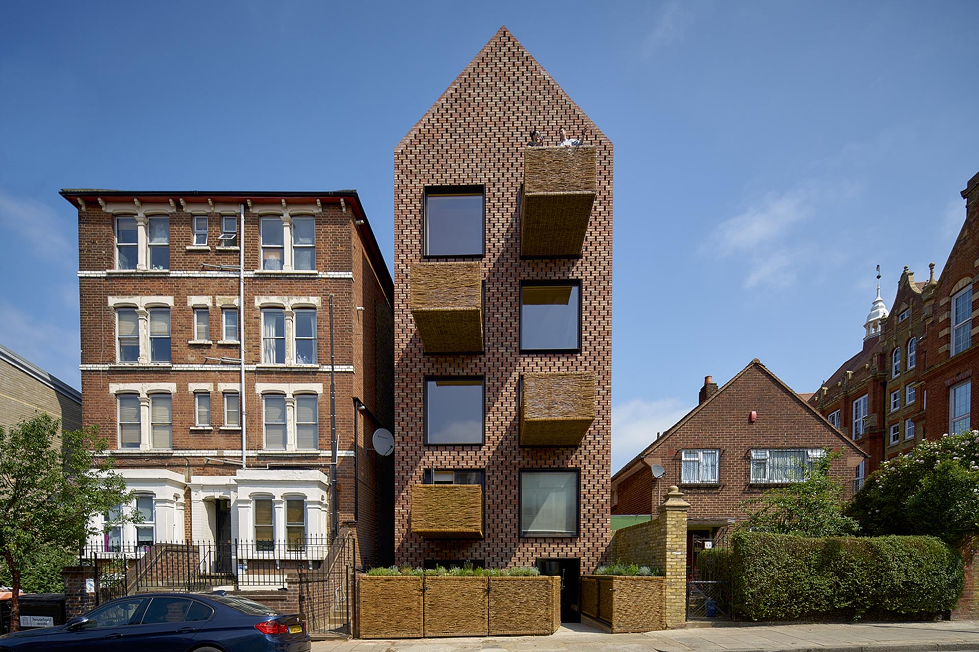 A brick building with steel window frames and protruding woven wicker balconies.