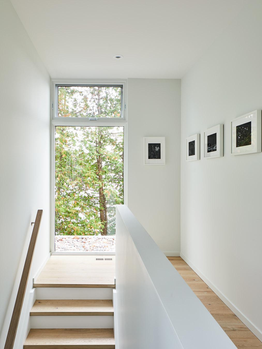 A white interior with wood stair treads and flooring.