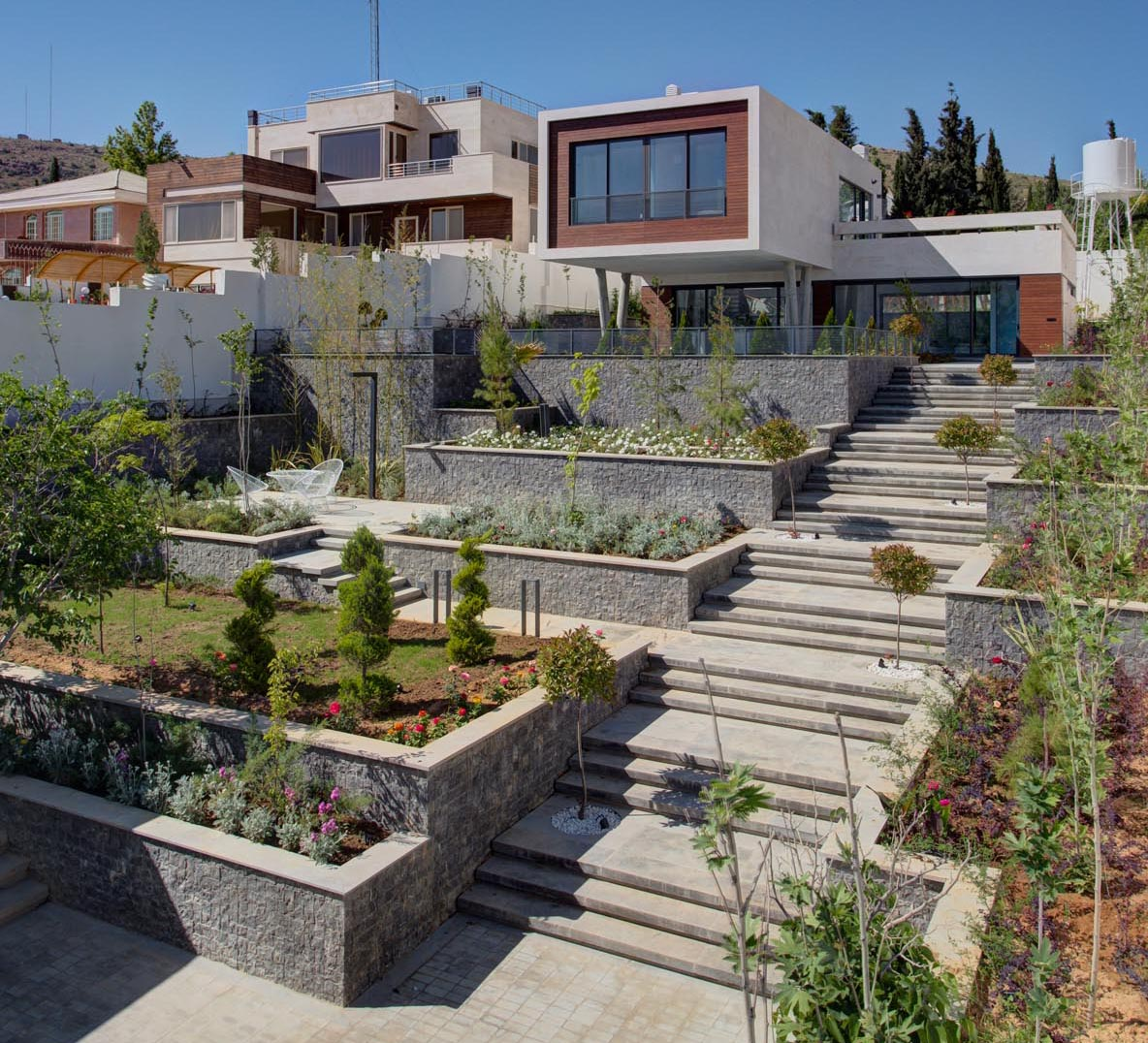 A terraced garden with wide stairs, sitting areas, and plenty of plants.