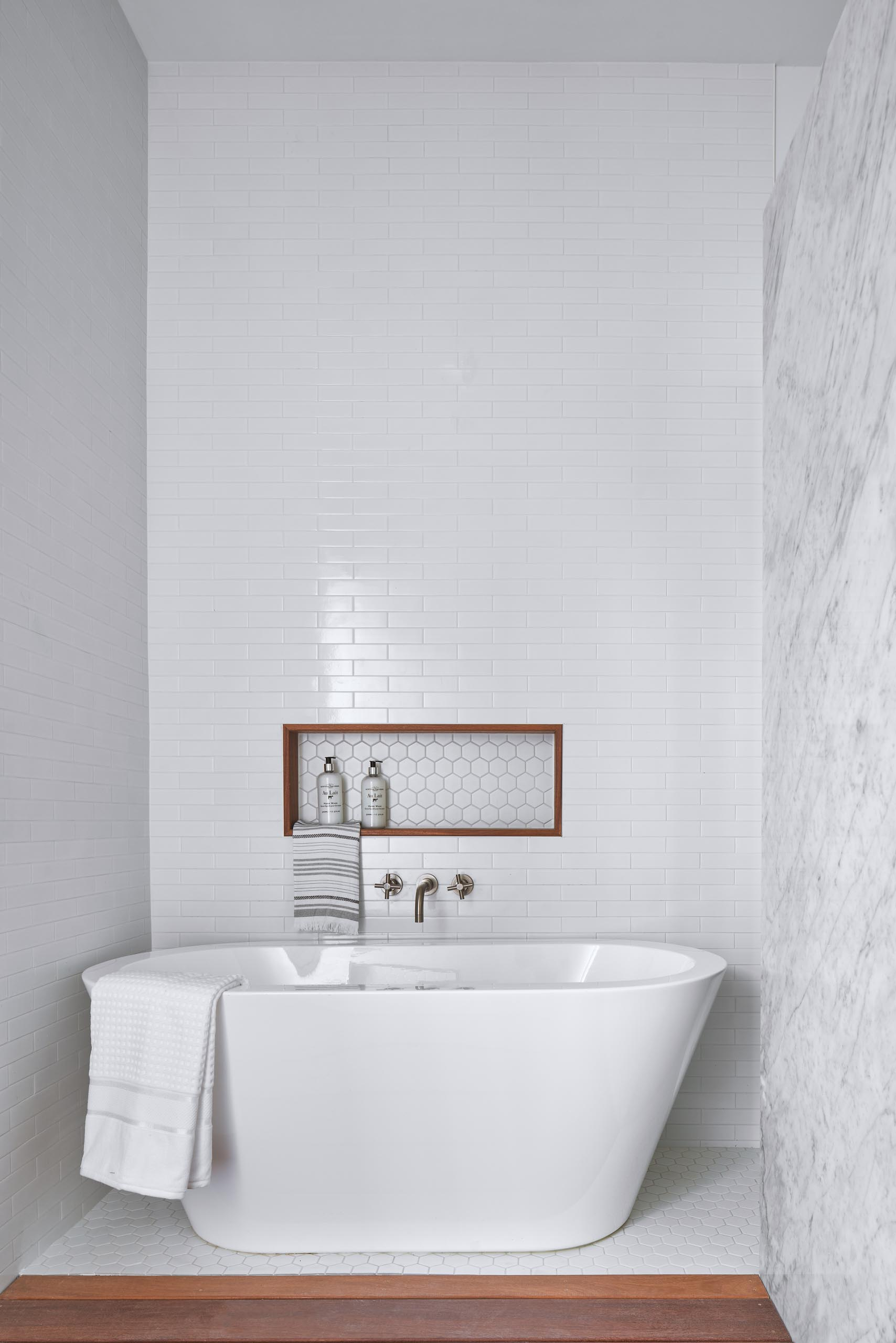 A white bathroom with a freestanding bathtub and shelving niche.