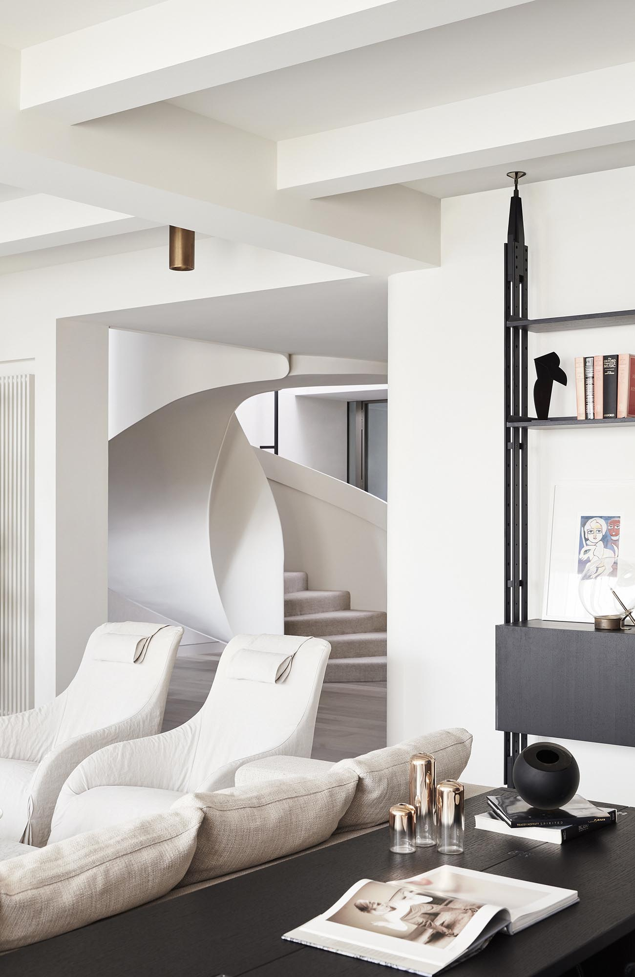 A modern interior with bright furniture and white spiral stairs.