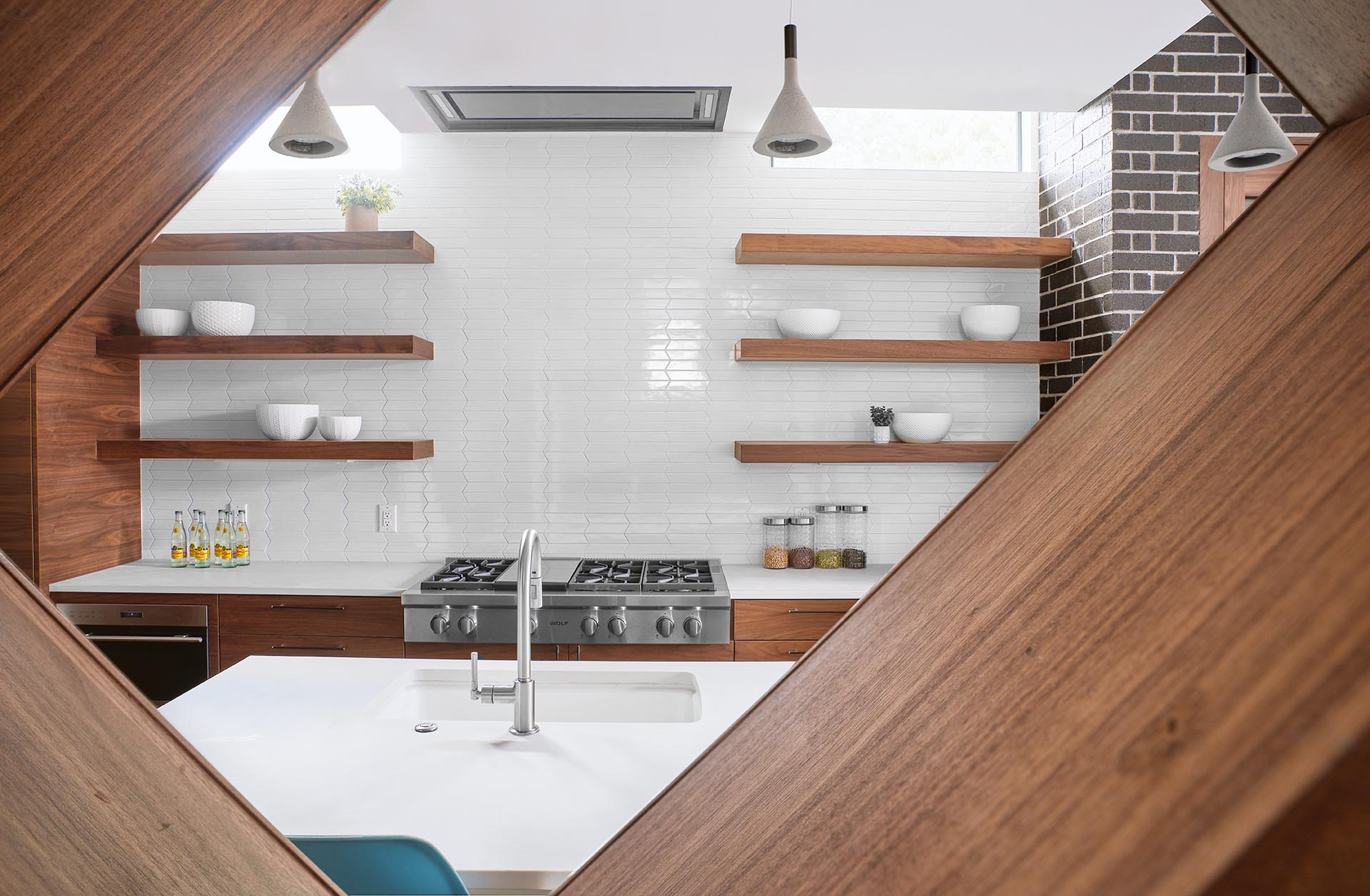 A open wood shelf provides a view of a modern kitchen.