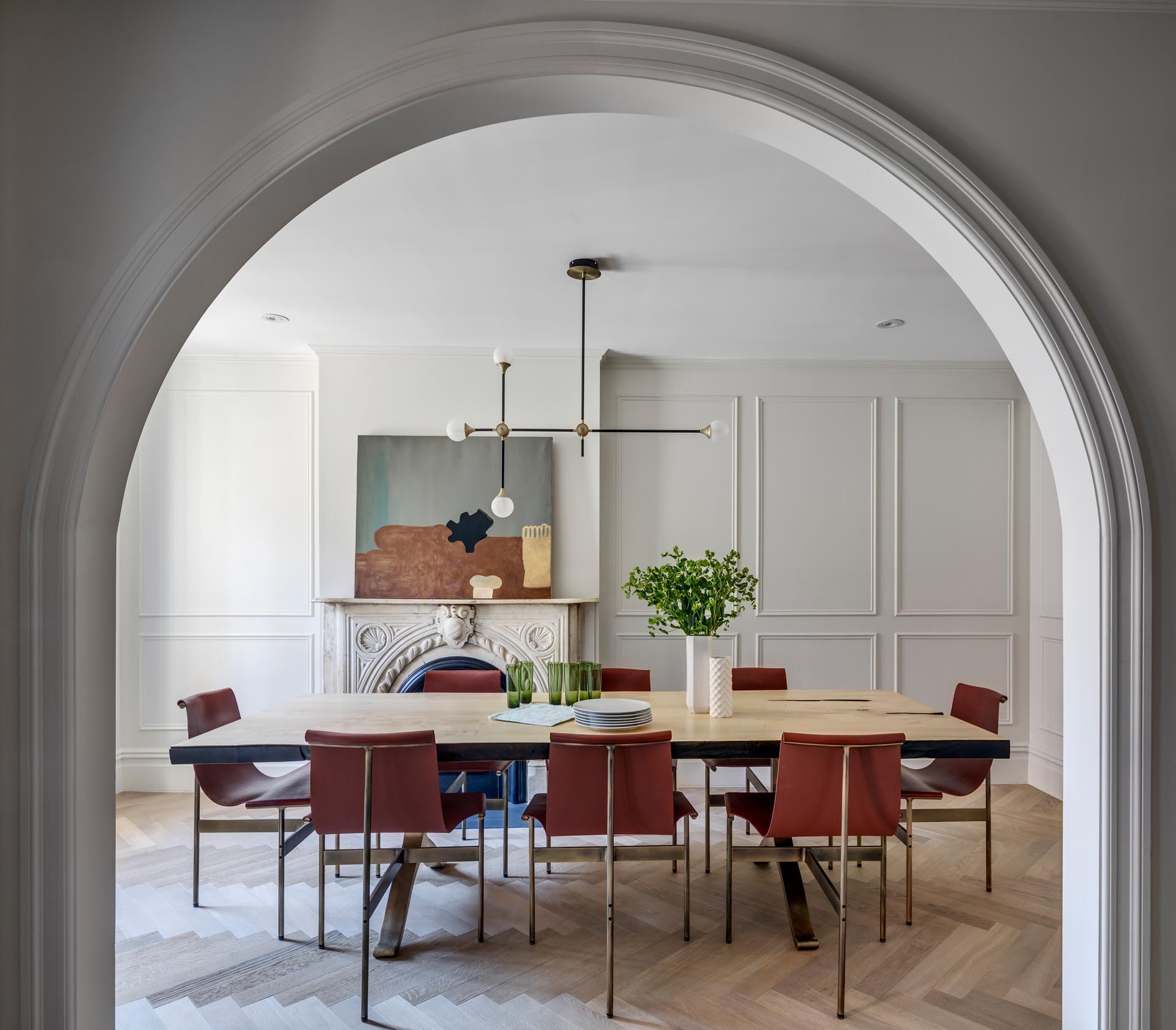 A dining room with a large wood table, an arched doorway, and a fireplace.