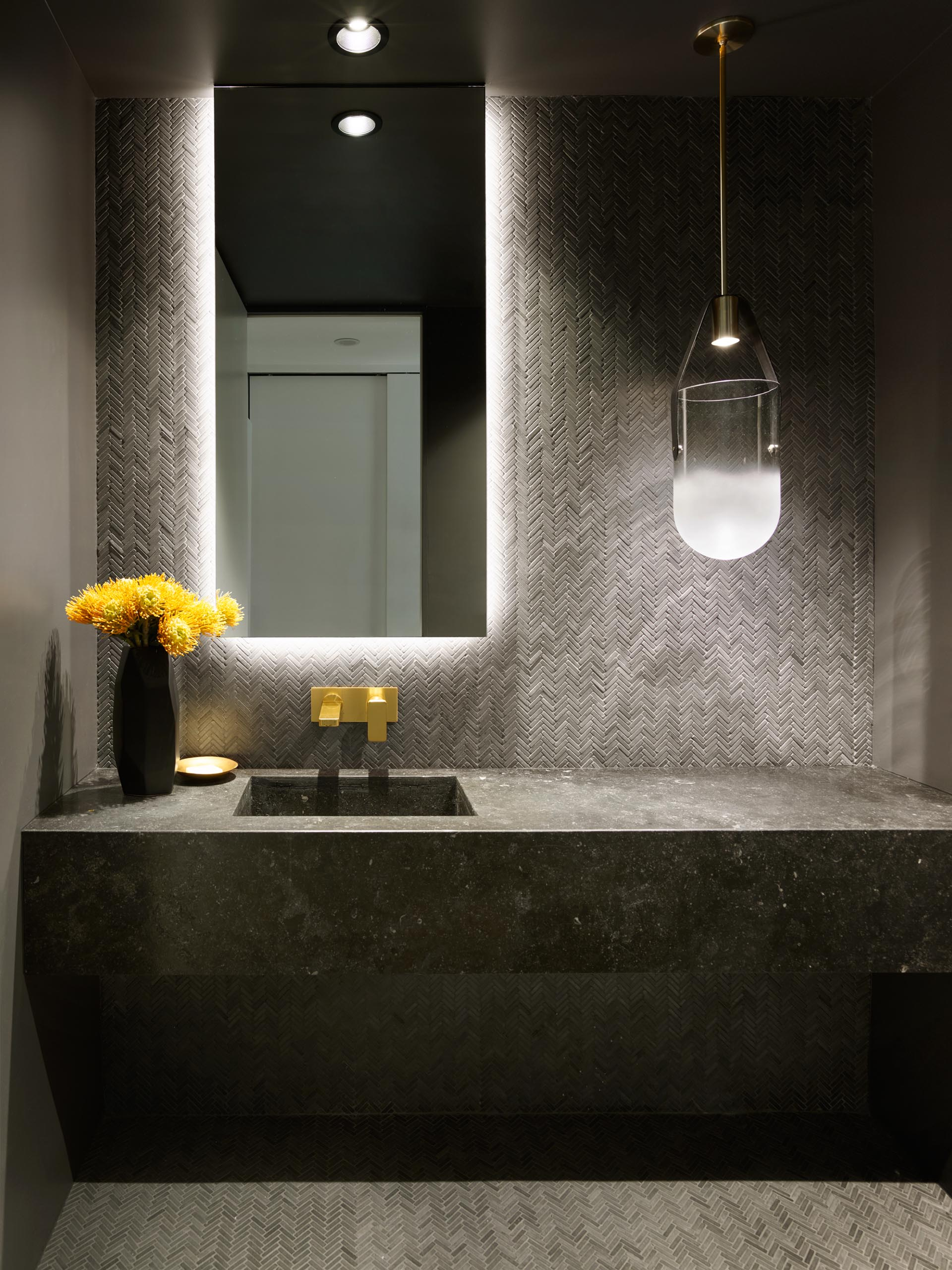 A modern powder room with dark grey tiles, a backlit mirror, and a glass pendant light.
