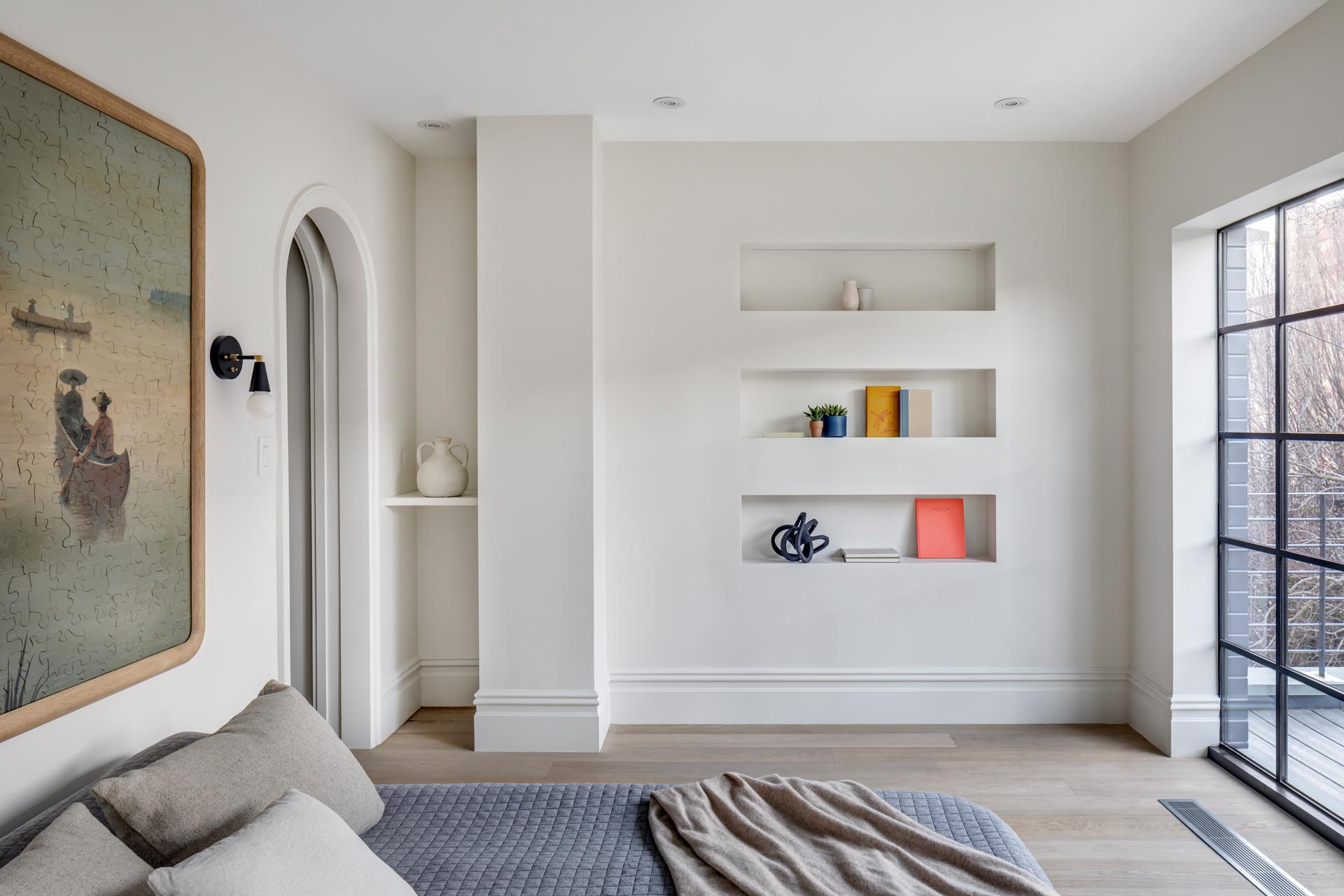 A modern master bedroom with built-in shelving niches, and an arched doorway.