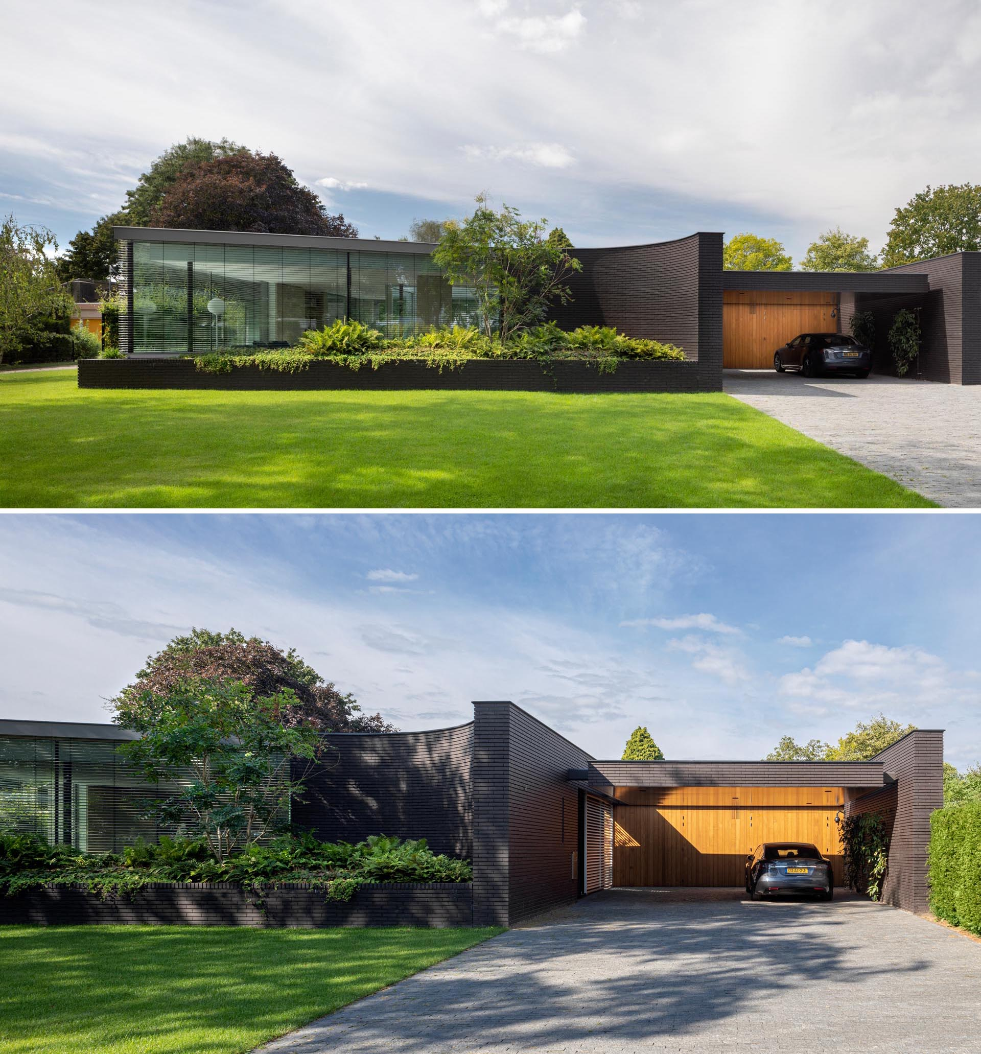 The black brick facade of this modern home features curves and has large integrated planters that highlight the lush greenery.