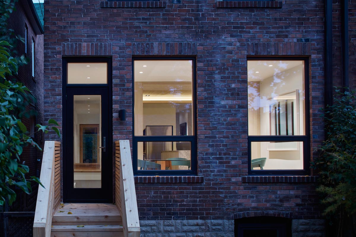 A brick house with black window frames and a modern interior.