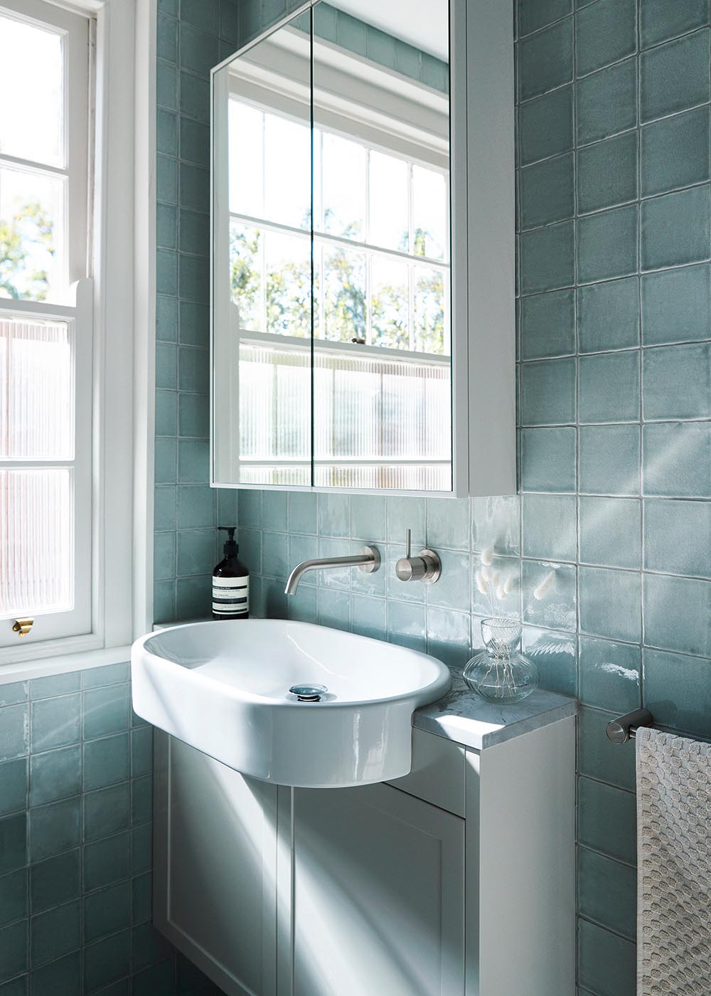 Soft blue handmade tiles employed in the bathroom offer a sense of restrained luxury.