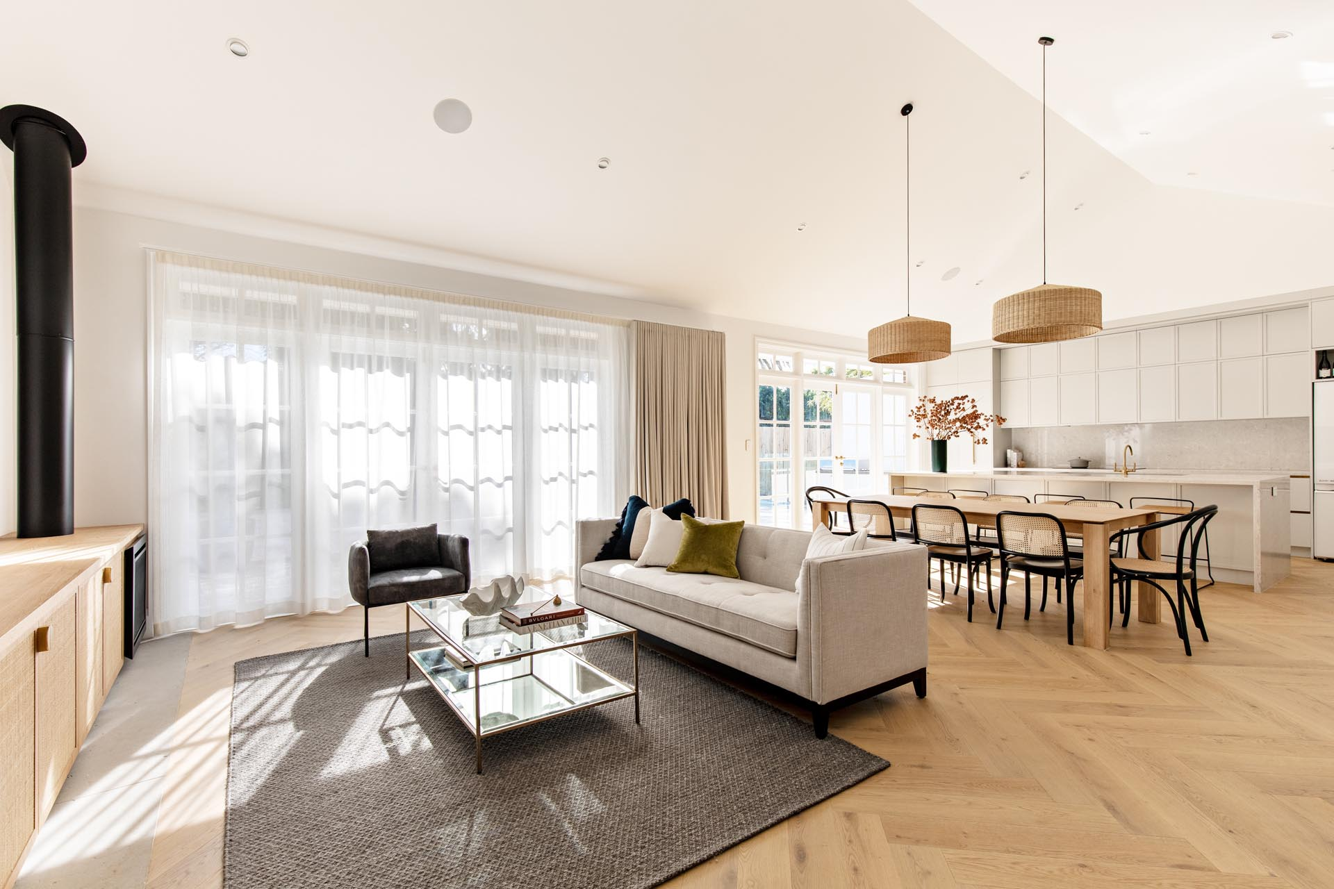 This contemporary open plan interior features a living room, dining area, and kitchen.