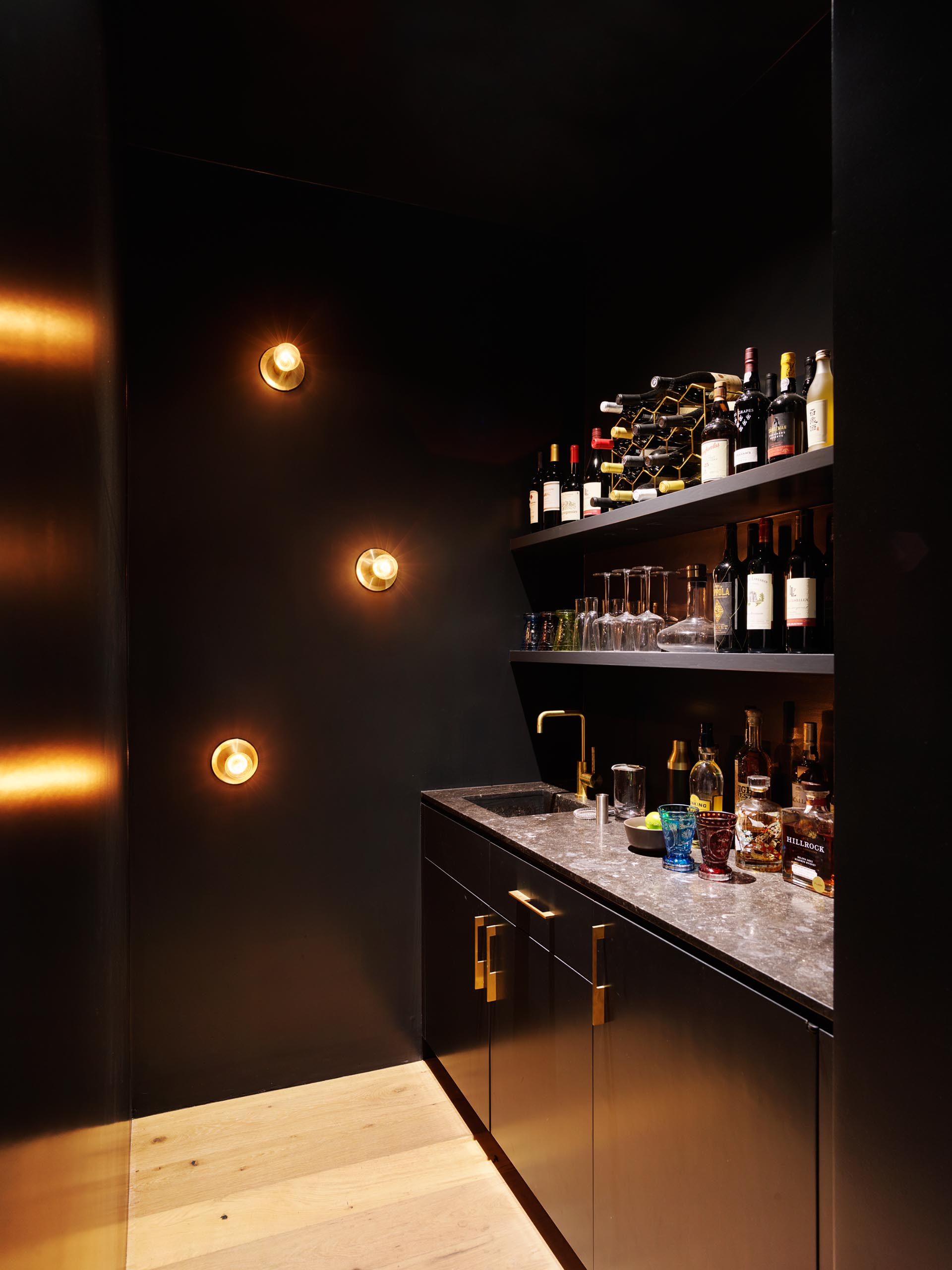 A small black home bar with shelving and cabinets.