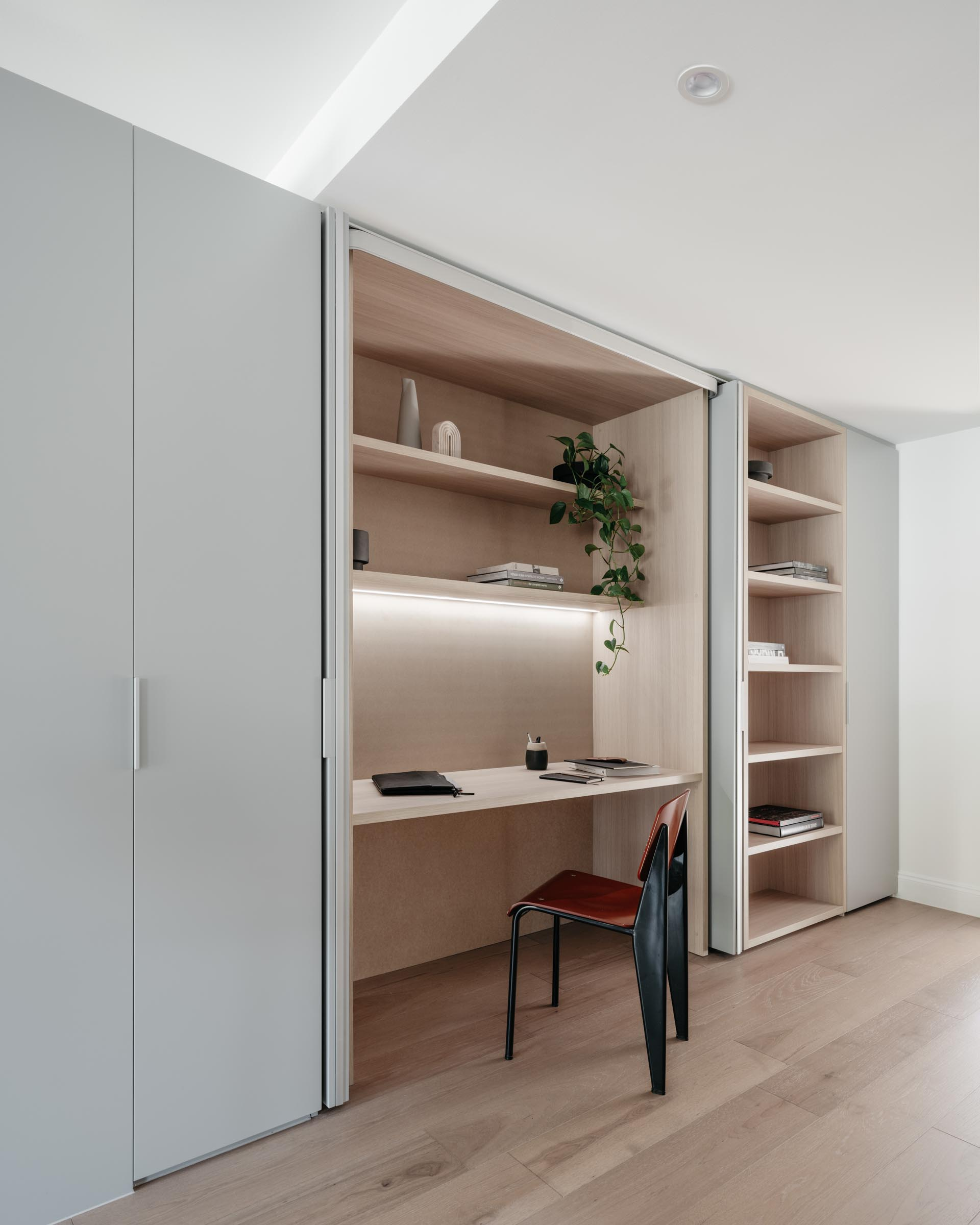A modern wood-lined home office hidden within a closet.