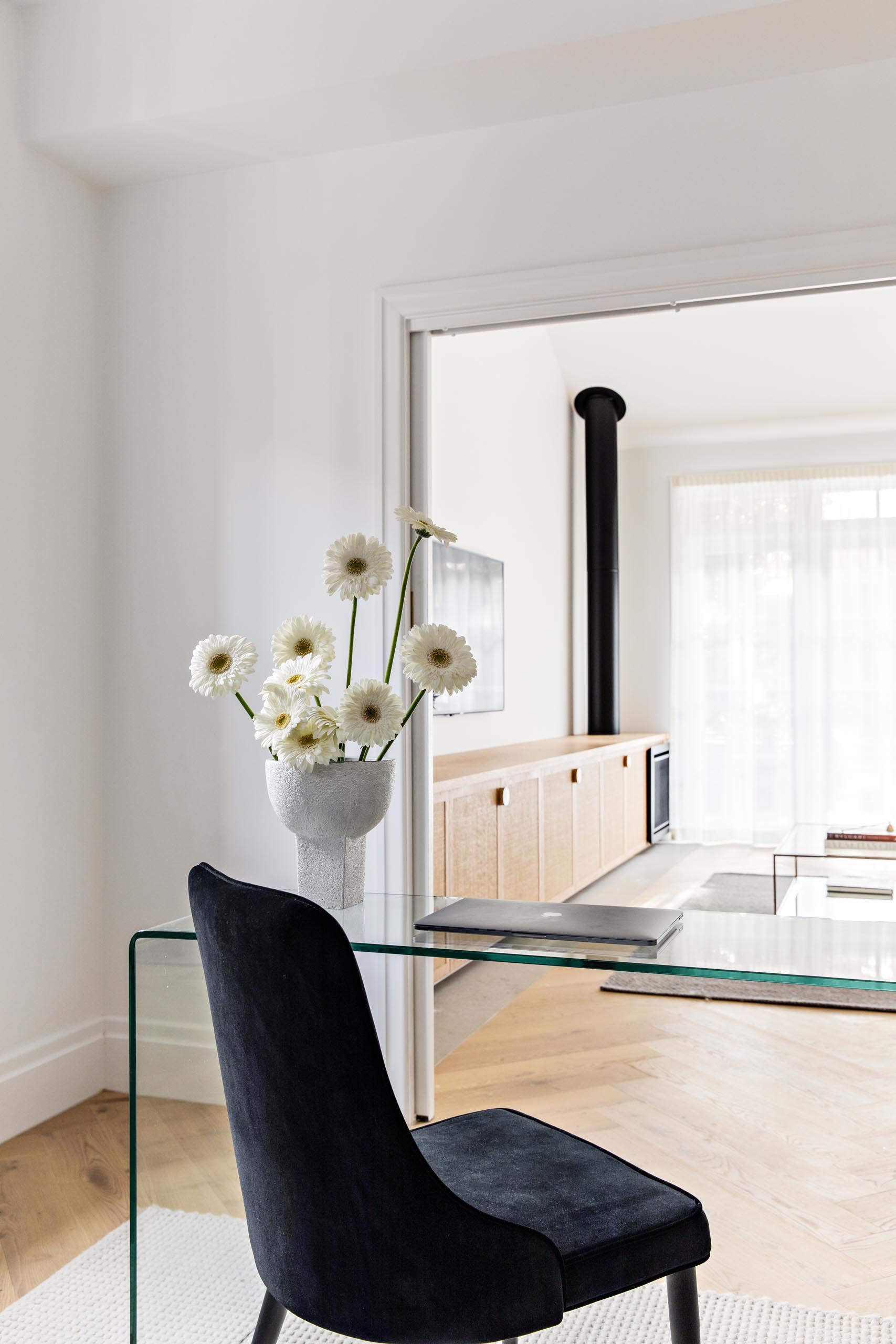 A modern home office with a glass desk, and an black upholstered chair.