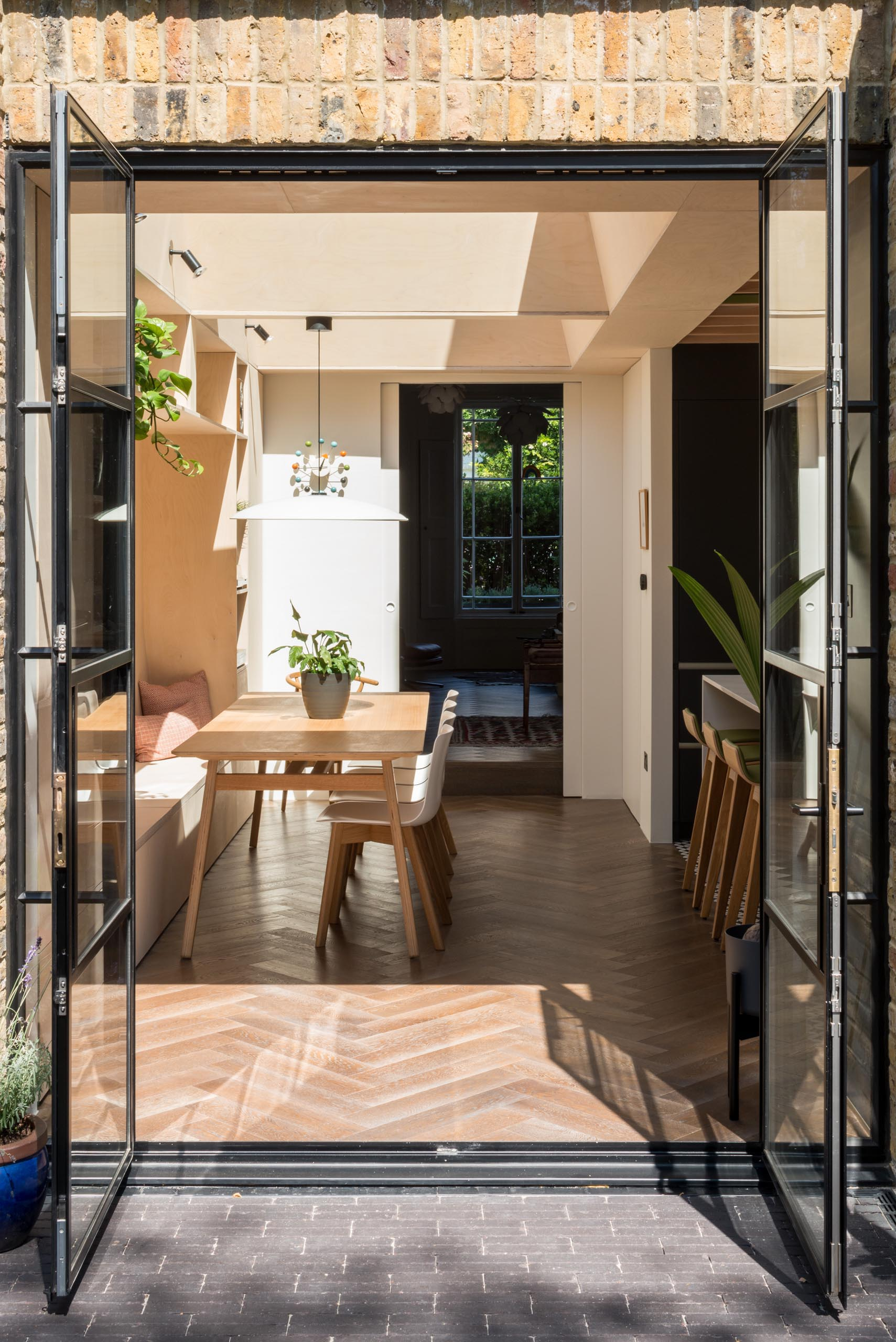 Black framed glass doors (Crittall doors) open to the garden.
