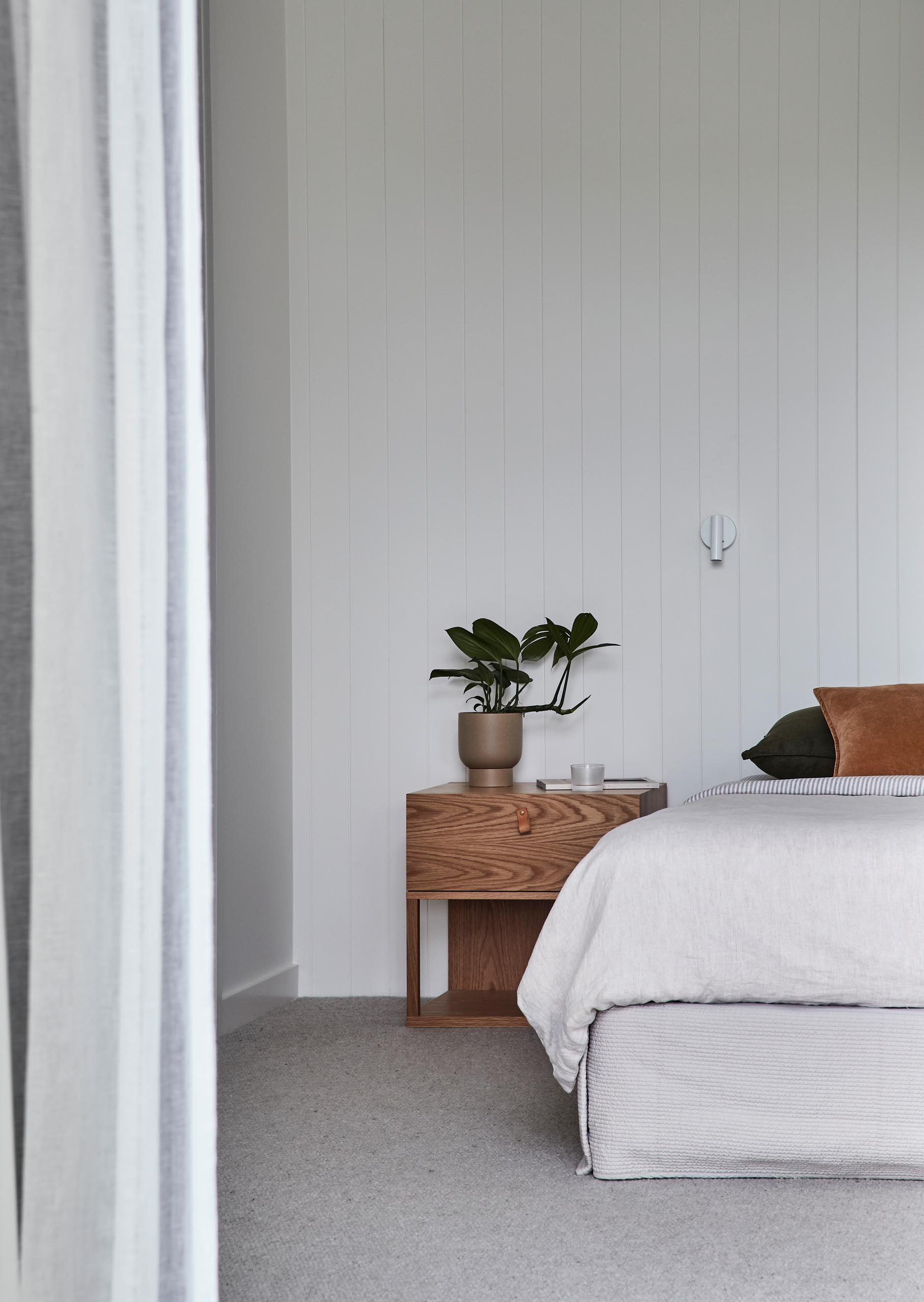 In this modern bedroom, the design has been kept minimal, while the wood and leather accents reference the other areas of the home.