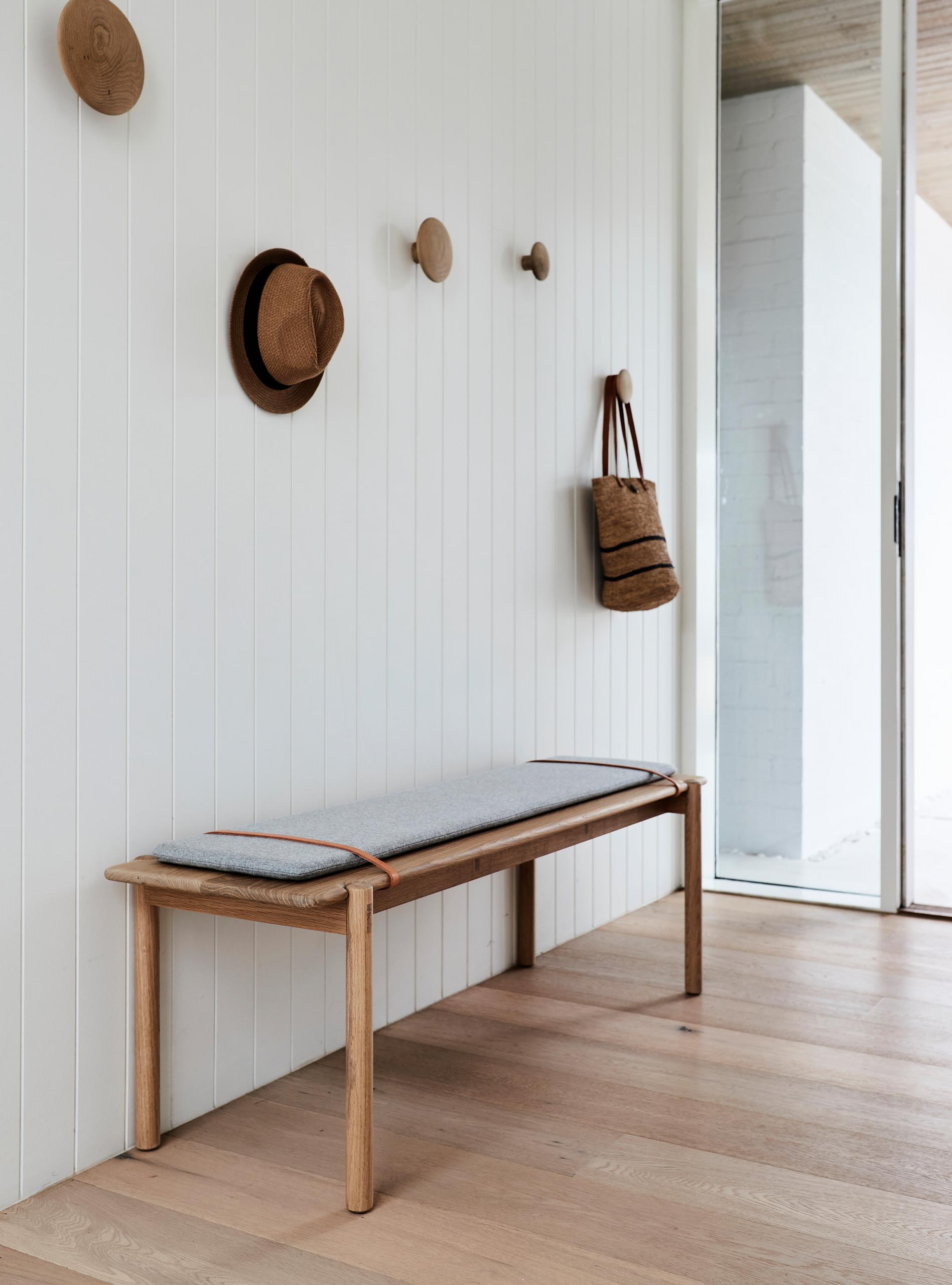 This modern entryway has a white wall, oak floors, a simple bench, and round wood wall hooks.