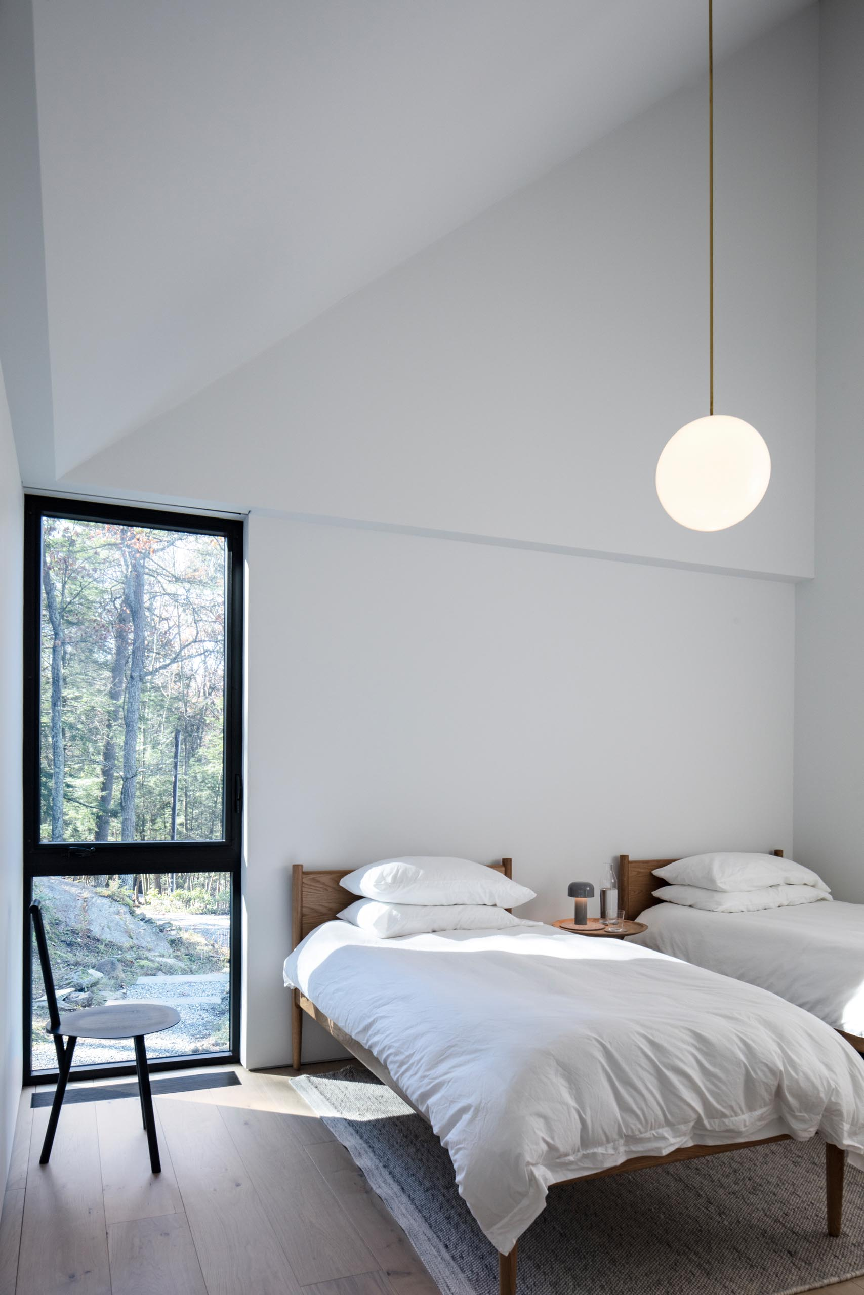 A minimalist guest bedroom with two beds, a modern black chair, white walls, and a single pendant light.