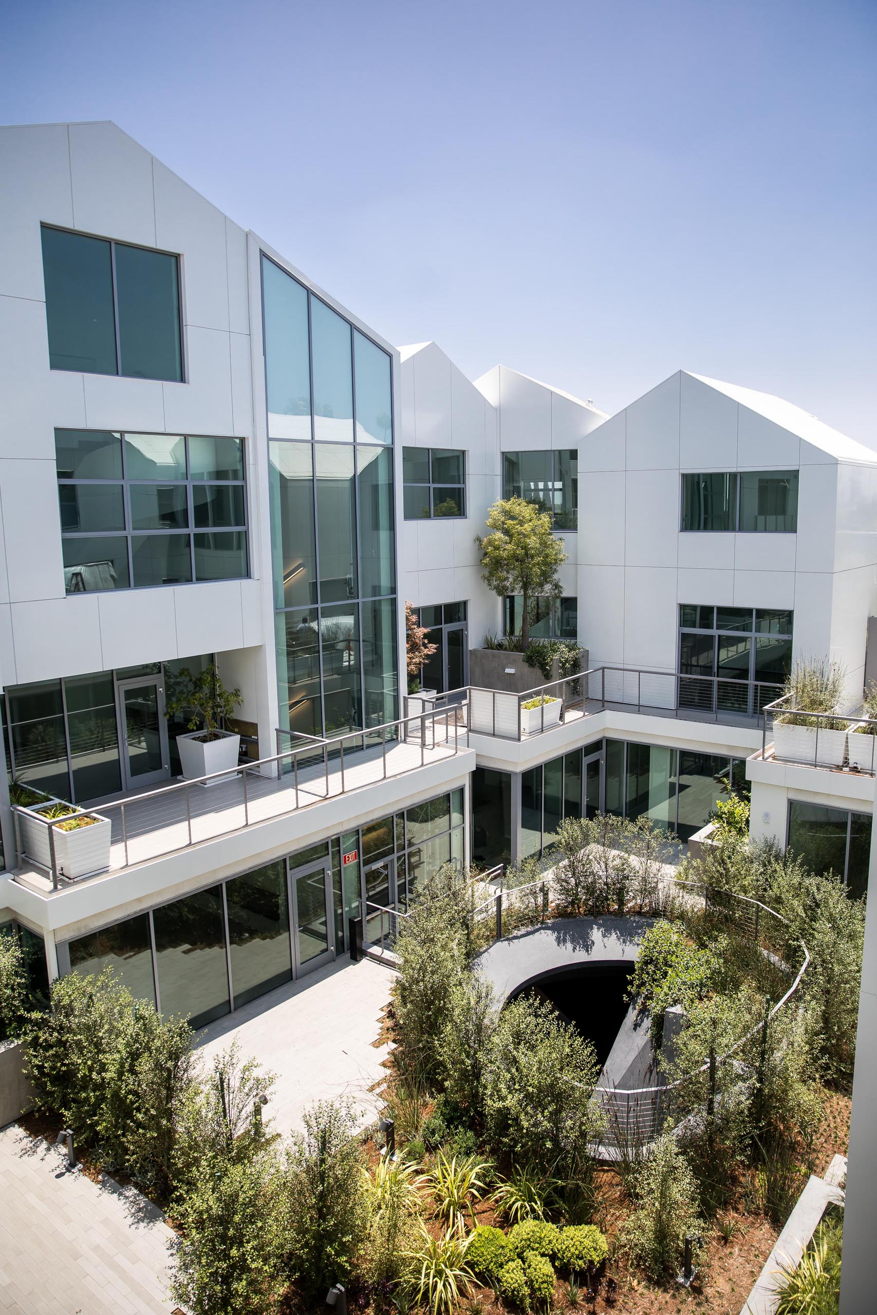 A modern residential building with terraces and gardens.