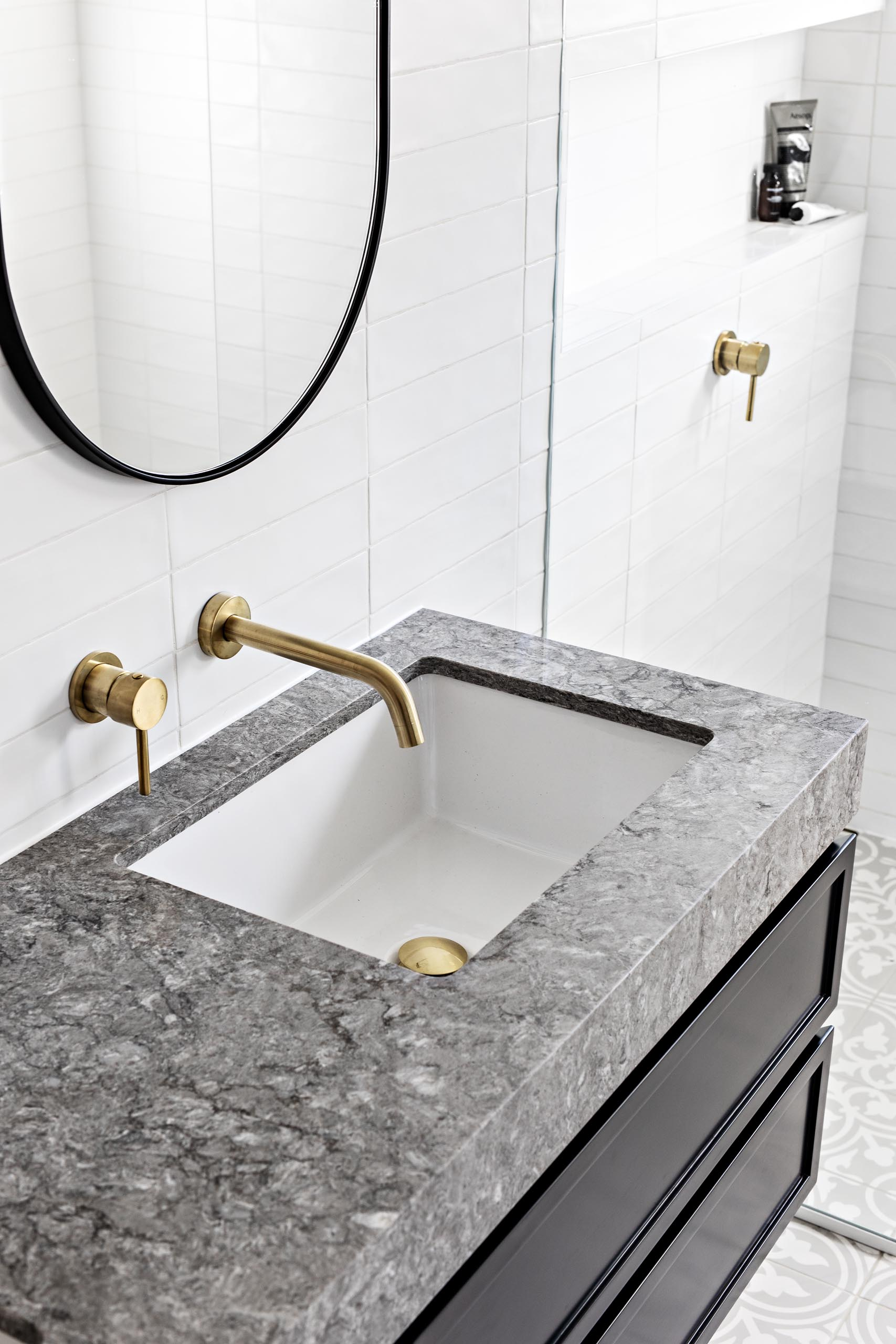 patterned floor tiles, a floating black vanity topped with grey stone, white subway tiles that cover the walls, oval black-framed mirrors, and brass hardware