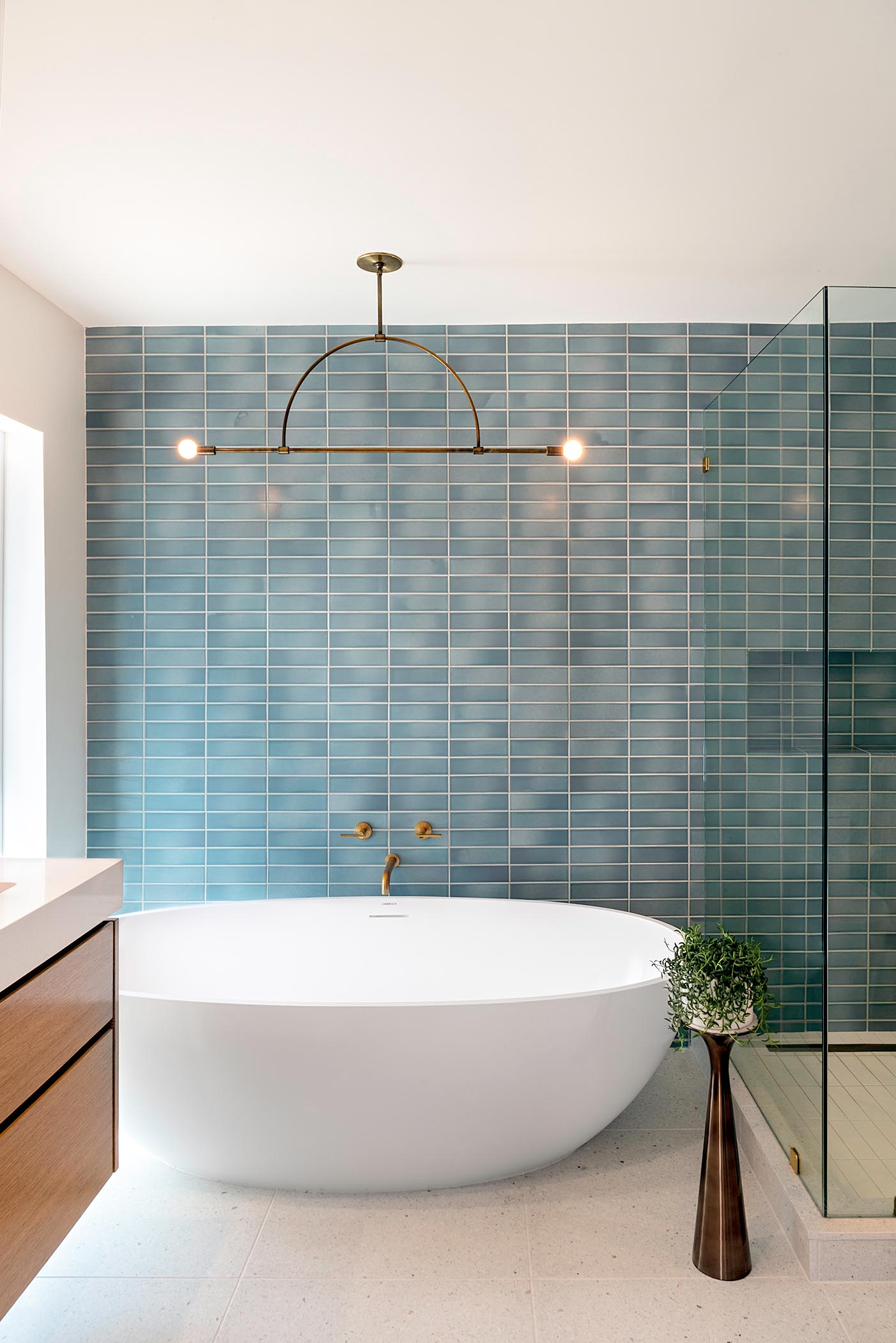 This modern bathroom with blue rectangular wall tile, a minimalist light fixture, a freestanding white bathtub, and brass fixtures.