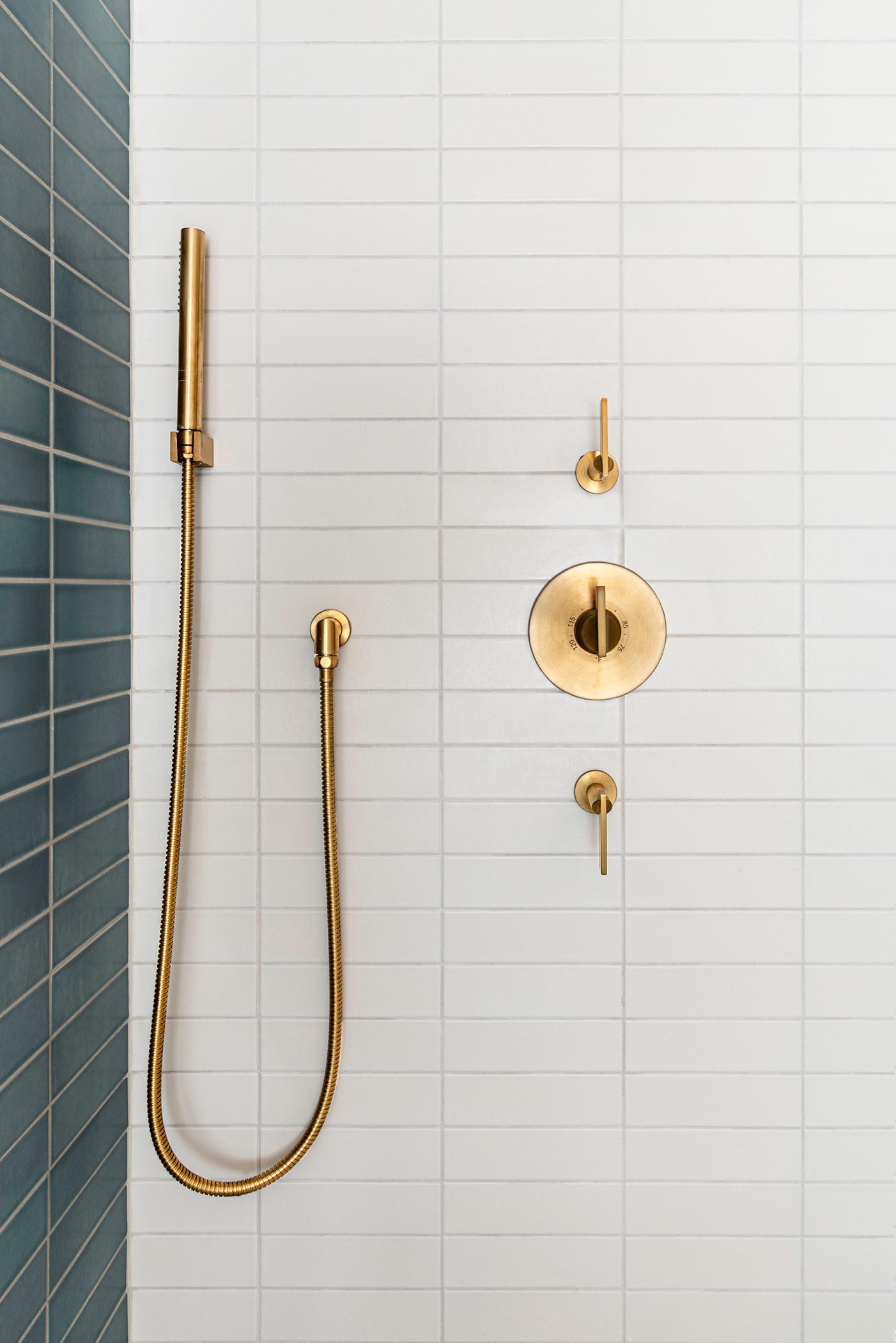 This modern bathroom with blue and white rectangular wall tile, a shower with a shelving niche, and brass fixtures.