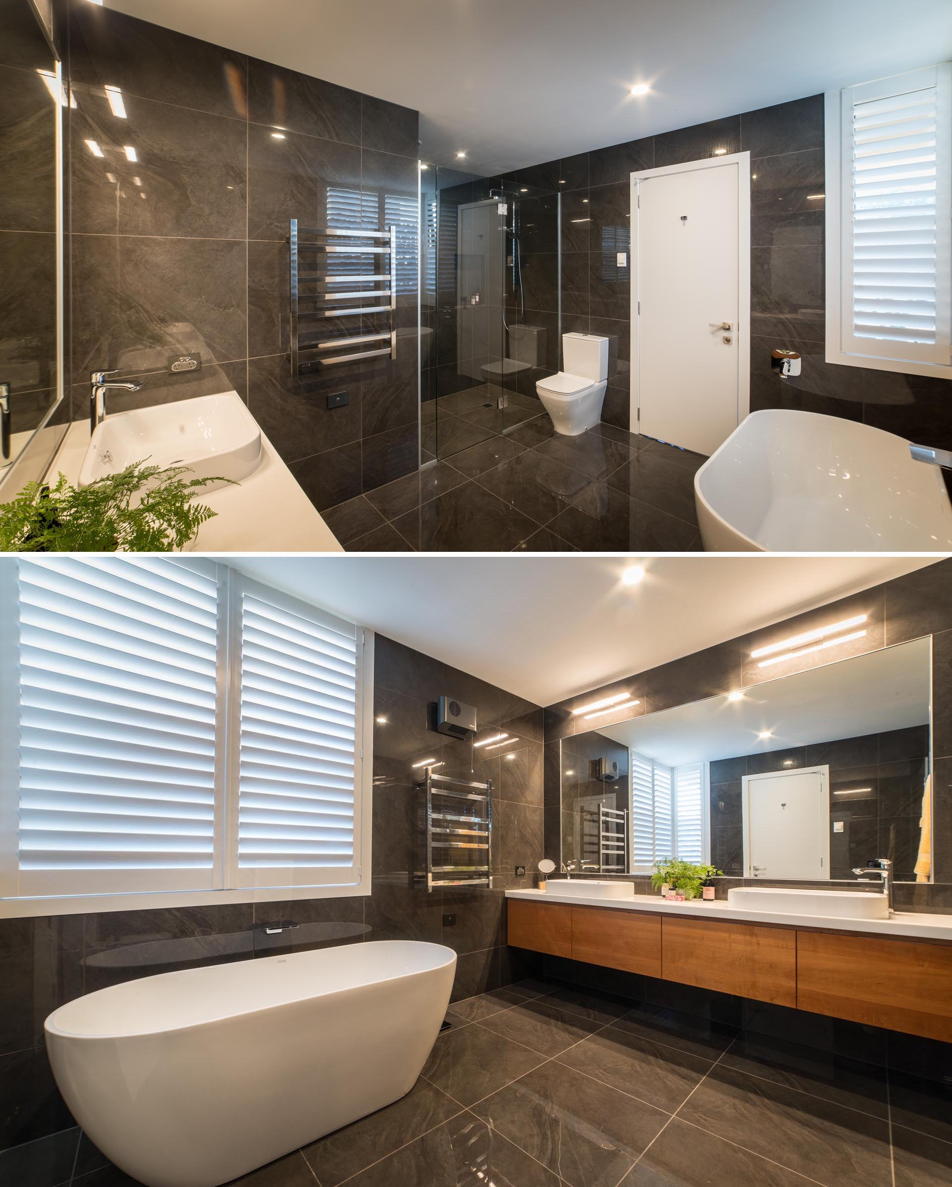 A modern master bathroom with large format dark colored tiles that cover the walls and floor, and a white freestanding bathtub and countertop that provide a contrasting element.