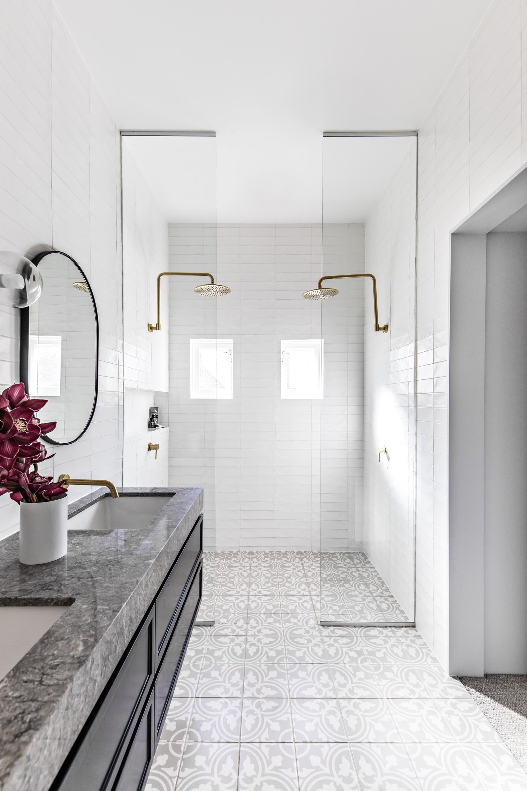 A modern bathroom with patterned floor tiles, a floating black vanity topped with grey stone, white subway tiles that cover the walls, oval black-framed mirrors, brass hardware, and floor-to-ceiling glass shower screens.