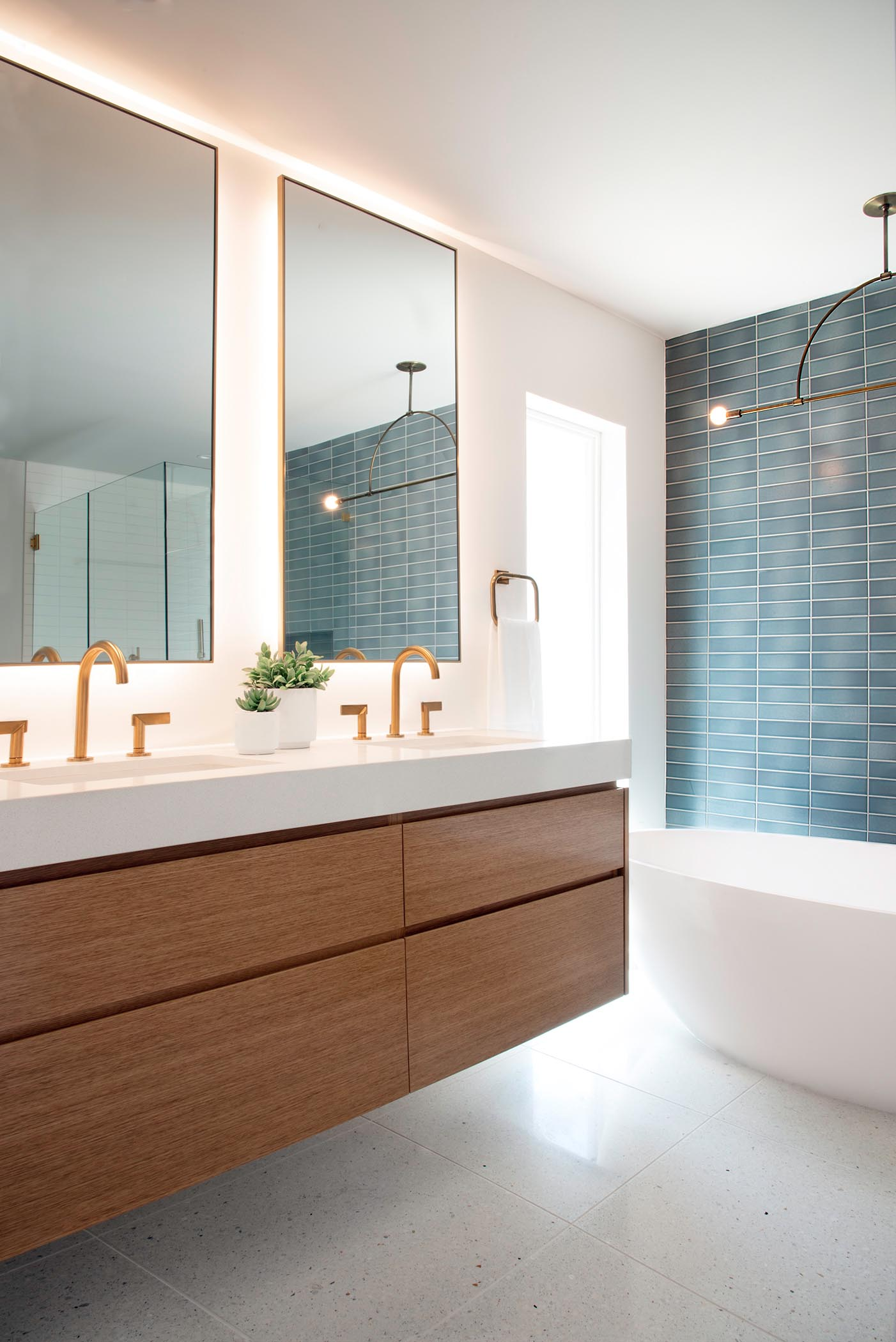 This modern bathroom includes a wall mounted wood vanity, blue and white rectangular wall tile, a minimalist light fixture, custom backlit mirrors, a freestanding white bathtub, and brass fixtures.