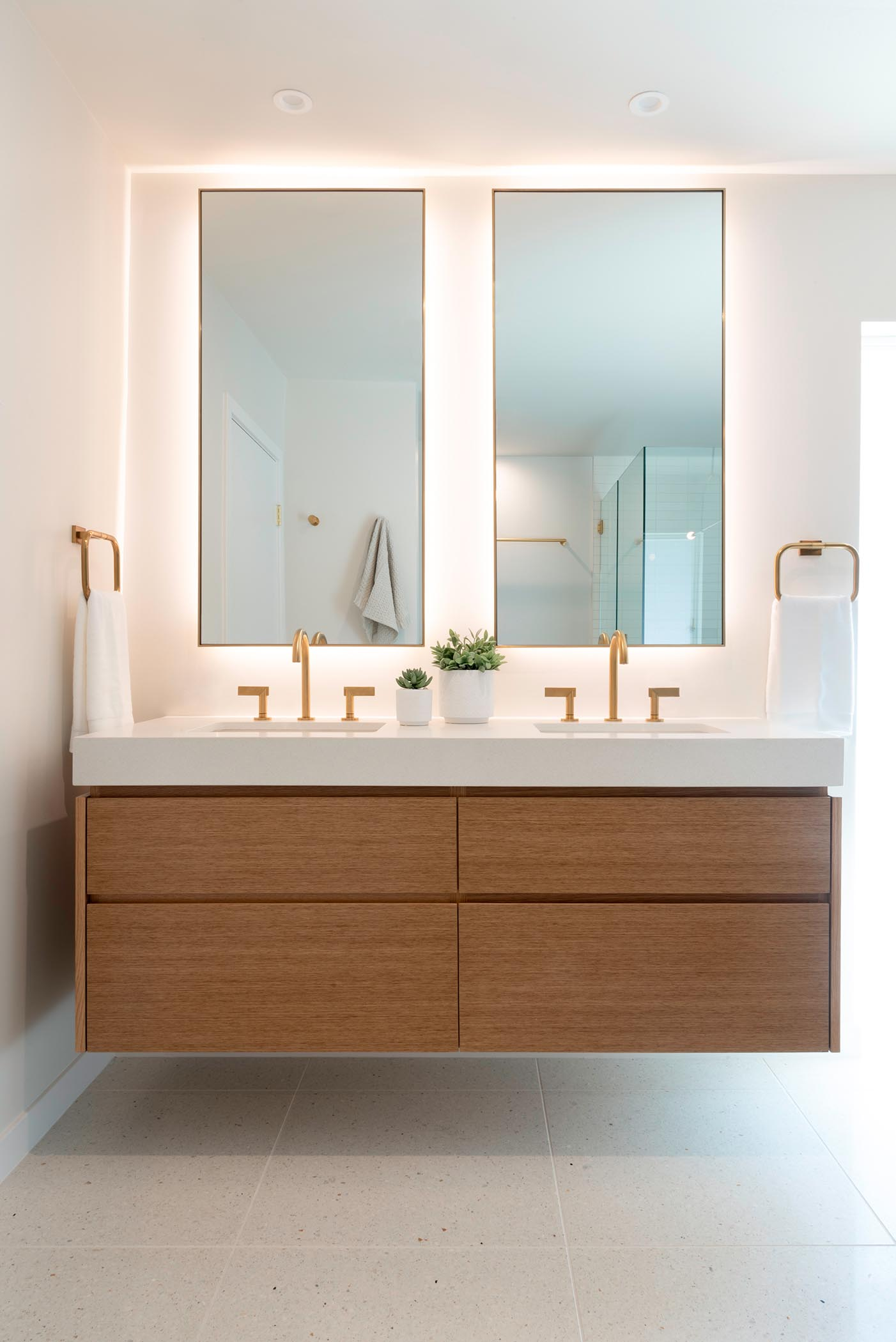 This modern bathroom includes a wall mounted wood vanity with custom backlit mirrors, and brass fixtures.