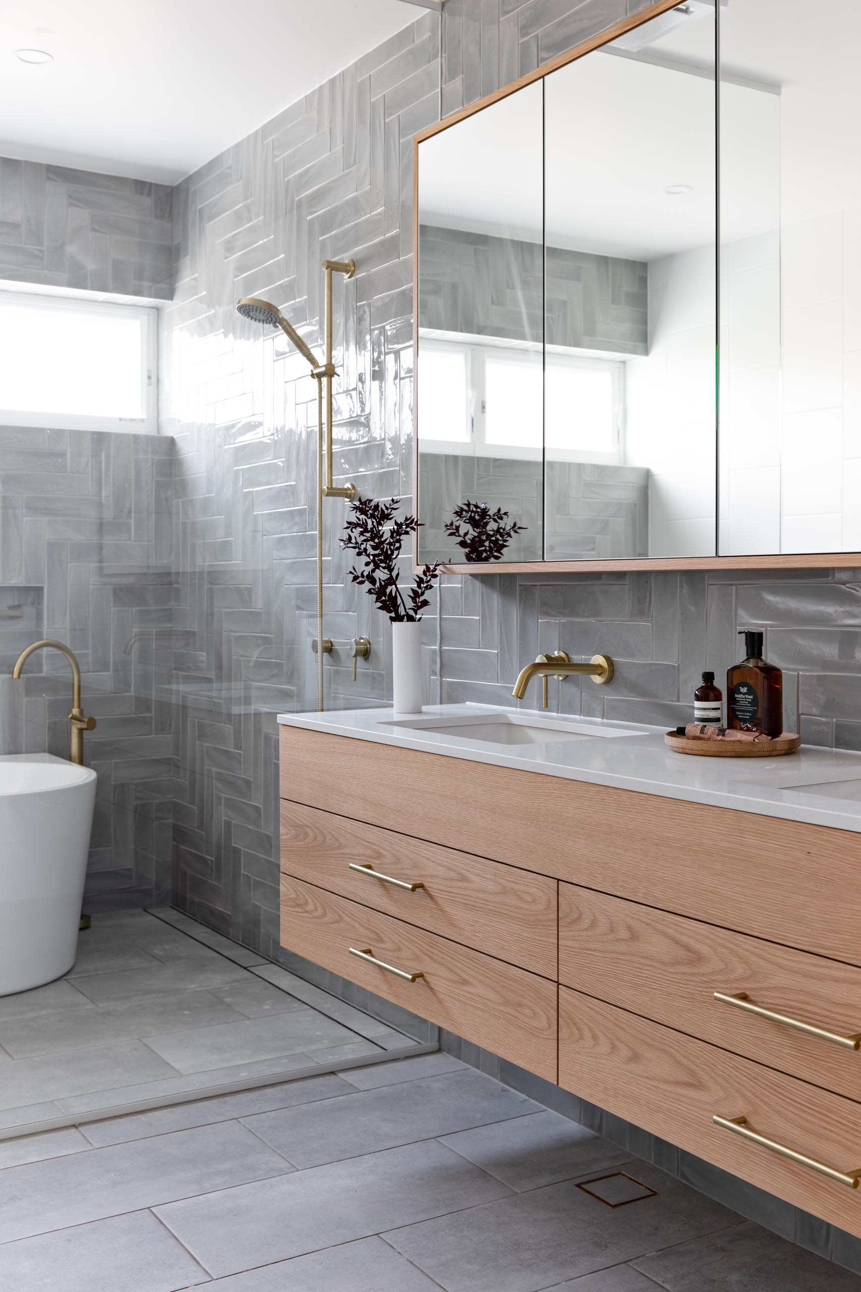 A modern bathroom with grey tiles installed in a herringbone pattern cover the wall, a floating wood vanity with a white countertop, and a glass shower screen that separates the shower and freestanding bathtub from the rest of the room.