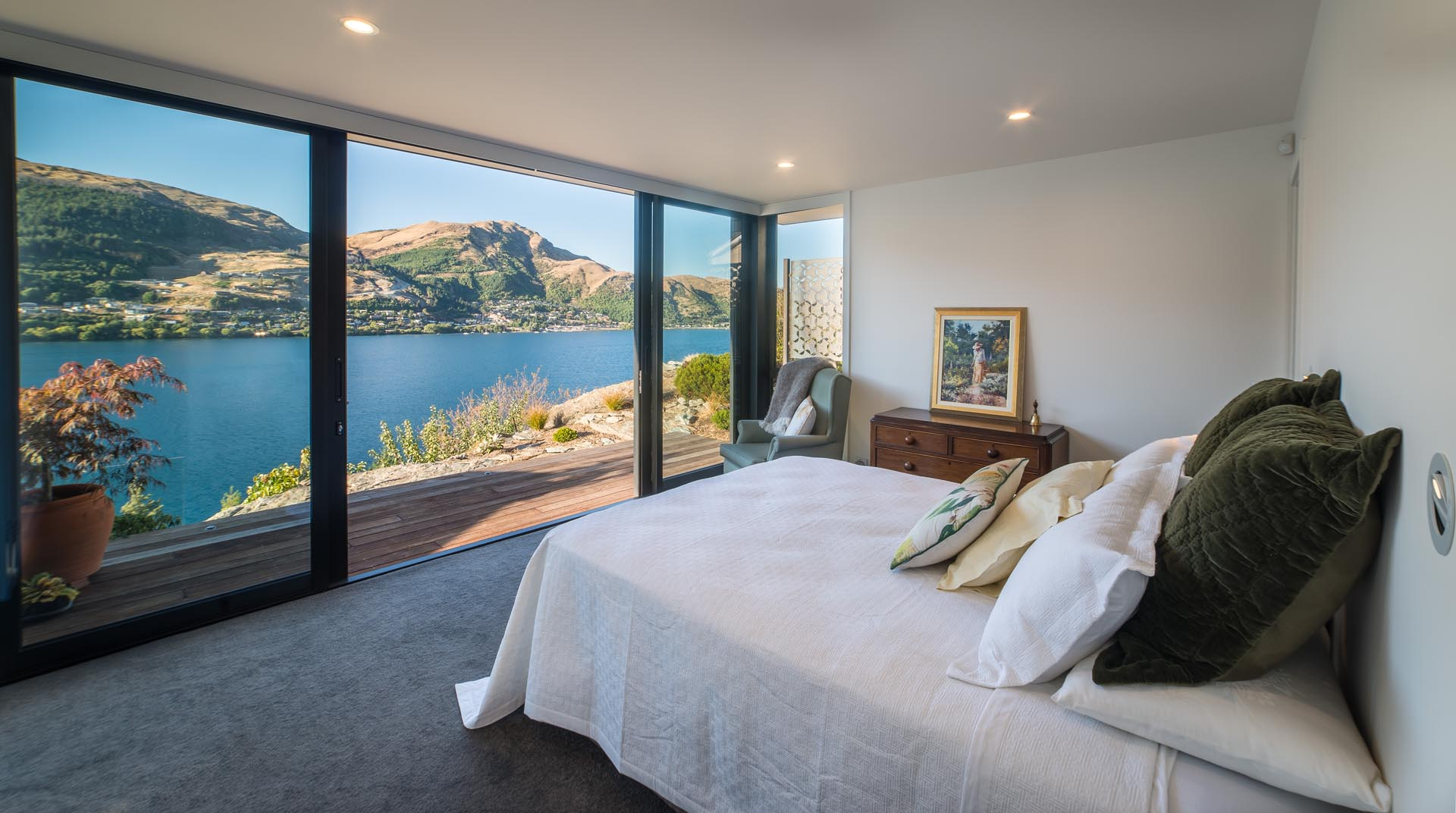 A modern bedroom with floor to ceiling windows and sliding glass doors, that provide an unobstructed view of the lake, which almost looks like a painting.