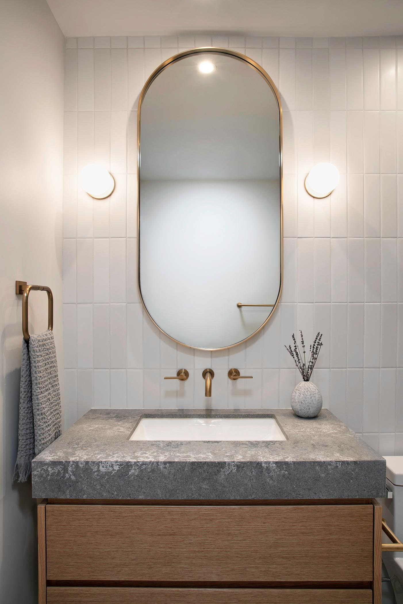 In this bathroom, there's a custom pill-shaped mirror flanked by specialty wall sconces, that hangs above a wood vanity with a grey countertop and white undermount sink.