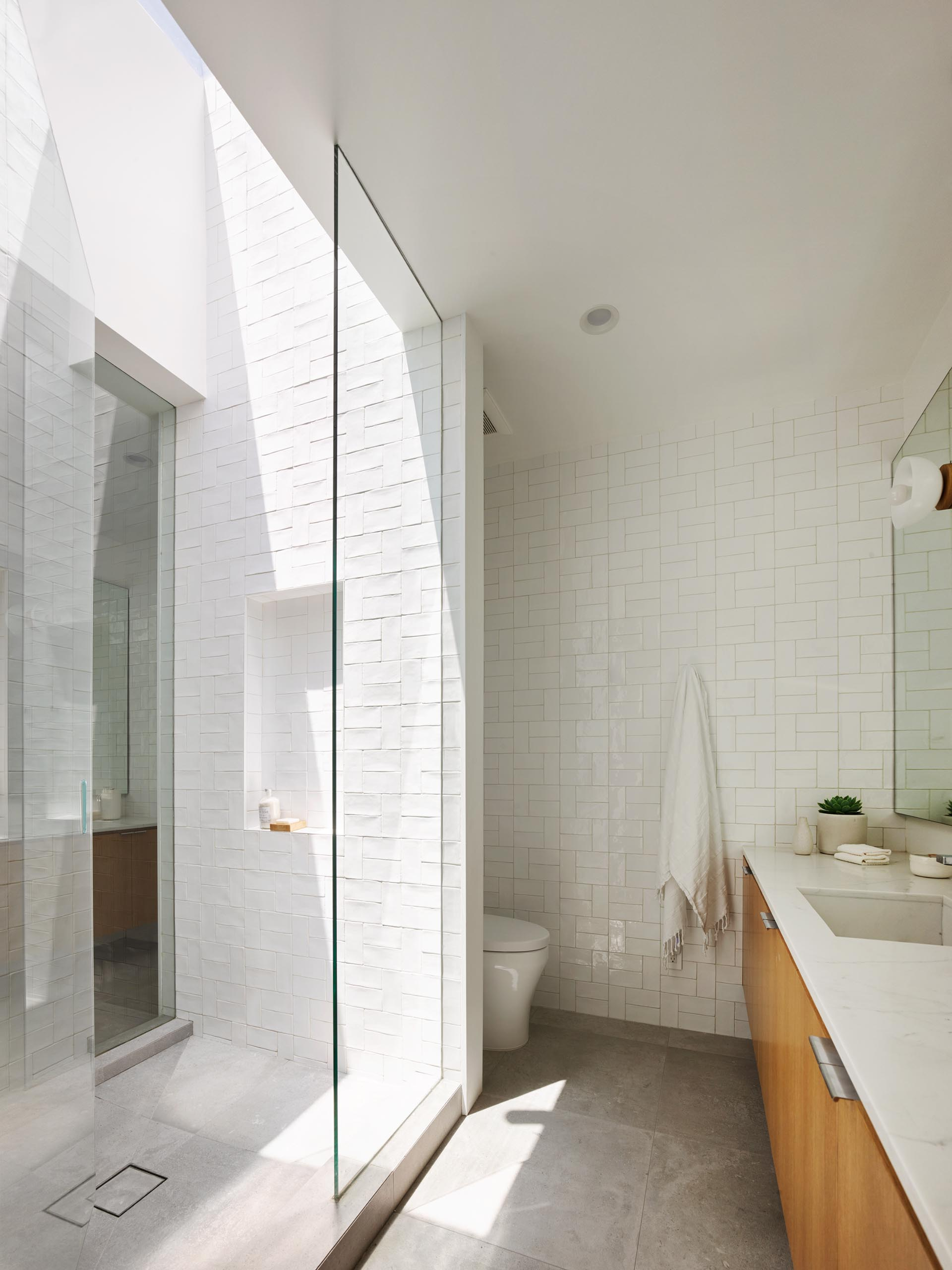 A modern bathroom with a walk-in shower with white tiles and a skylight, that adds plenty of natural light.