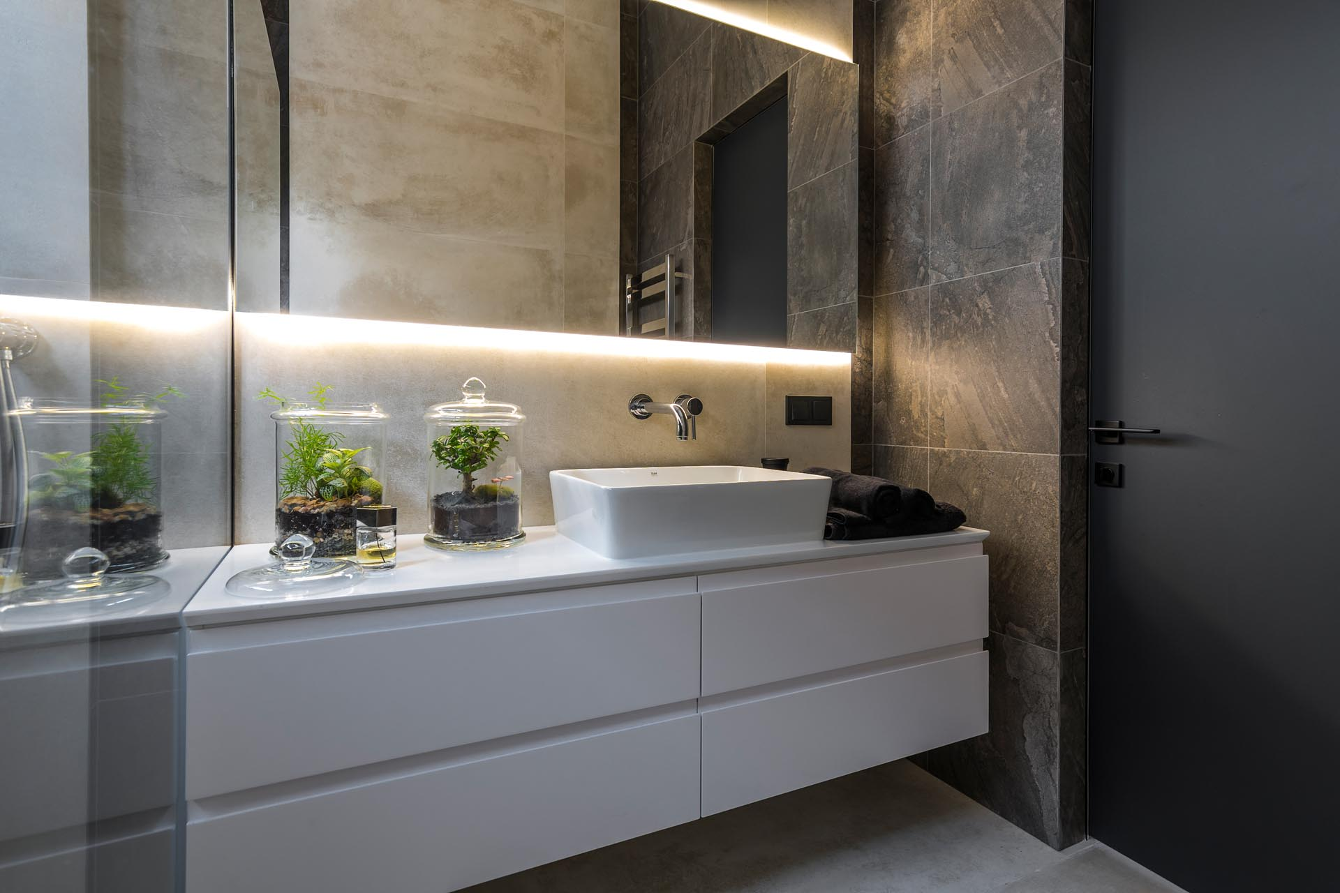A modern bathroom with a white vanity and a backlit mirror.